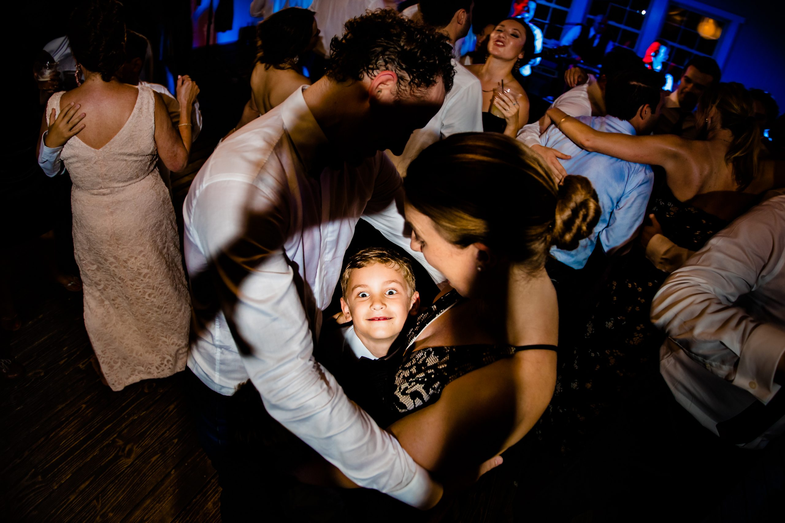 A young boy looks into the camera while on the dance floor