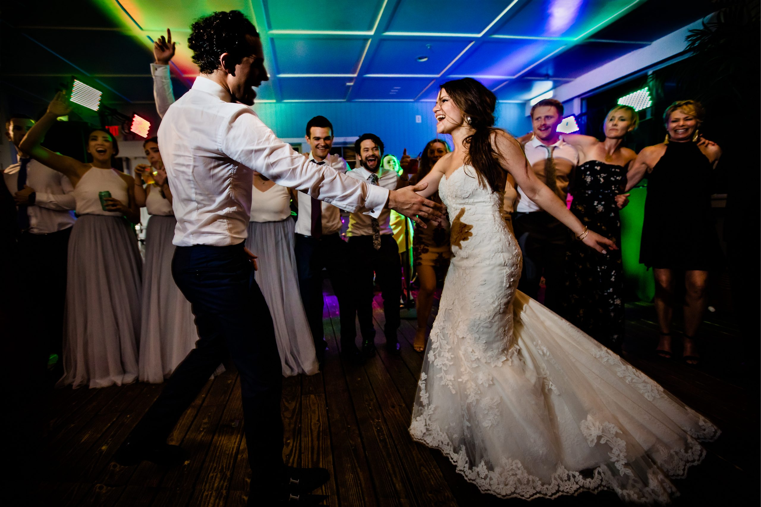 Bride and groom share a dance as friends cheer on
