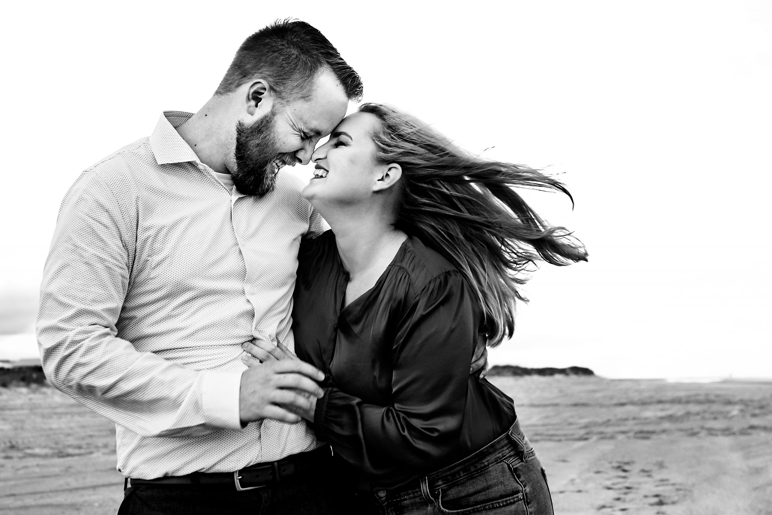 Couple look into each other's eyes on Emerald Isle beach.