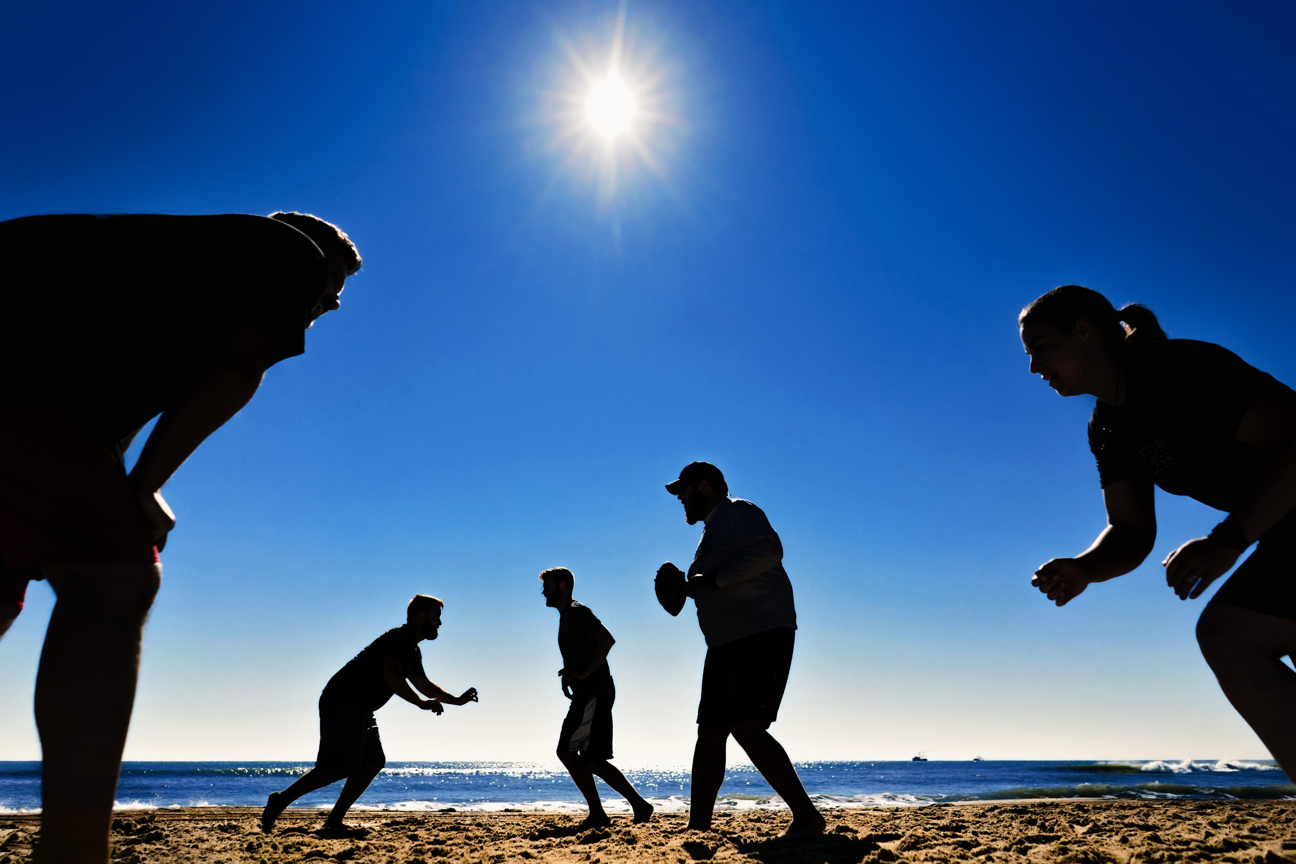 Wedding guests play football on the sun-soaked beach.
