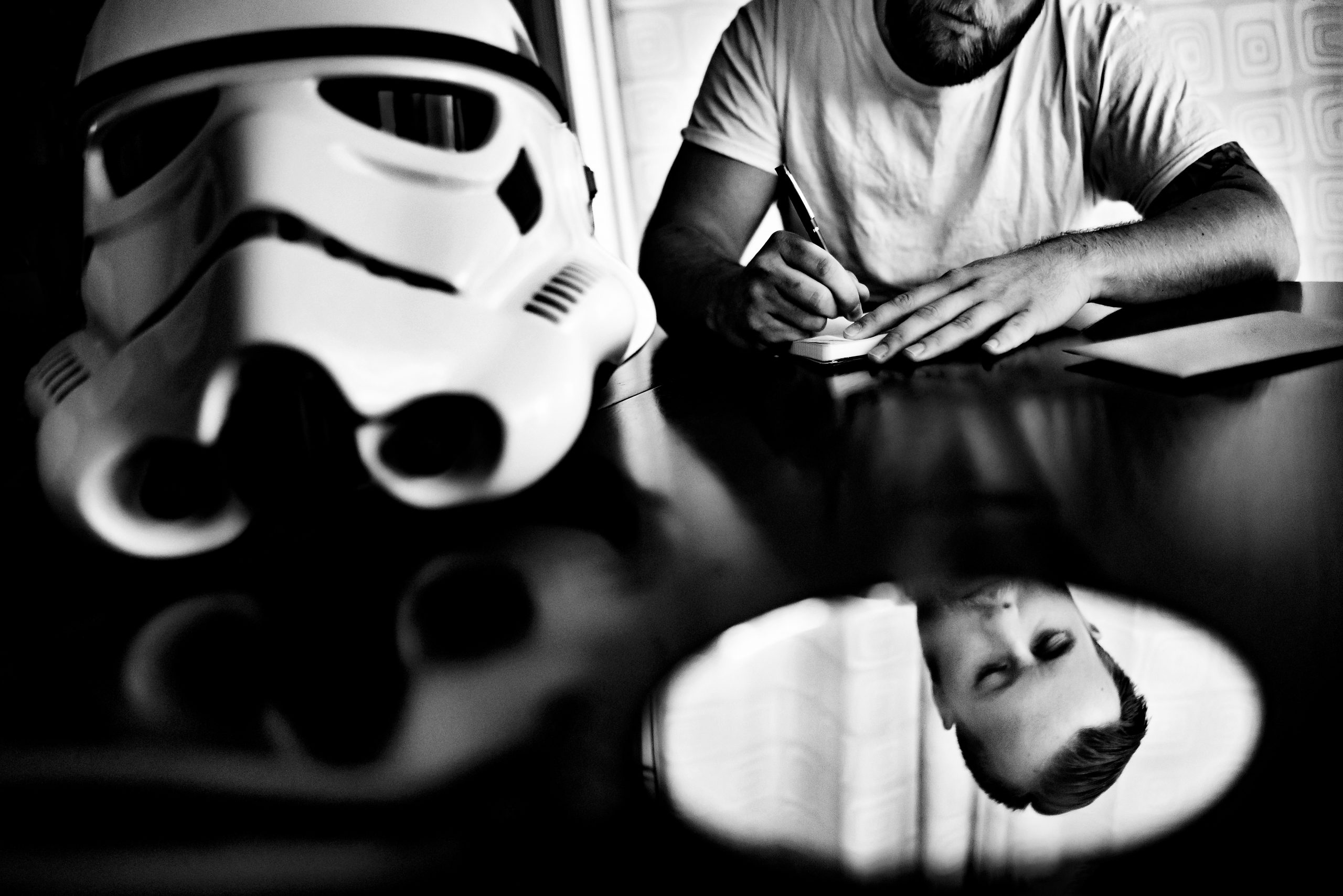 A Stormtrooper helmet sits on a desk as the groom reviews his wedding vows.