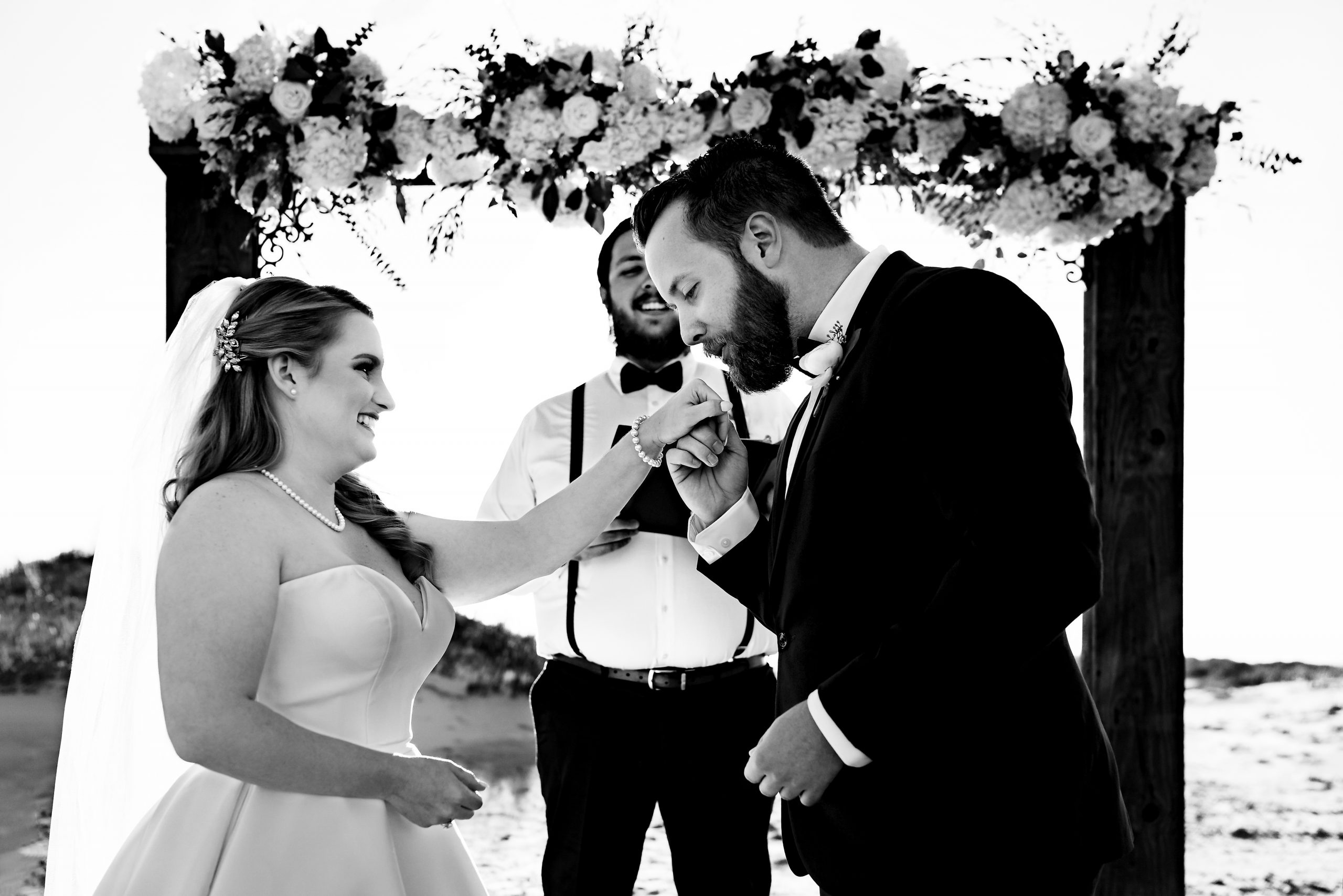 Groom reaches out to kiss the bride's hand at their wedding.