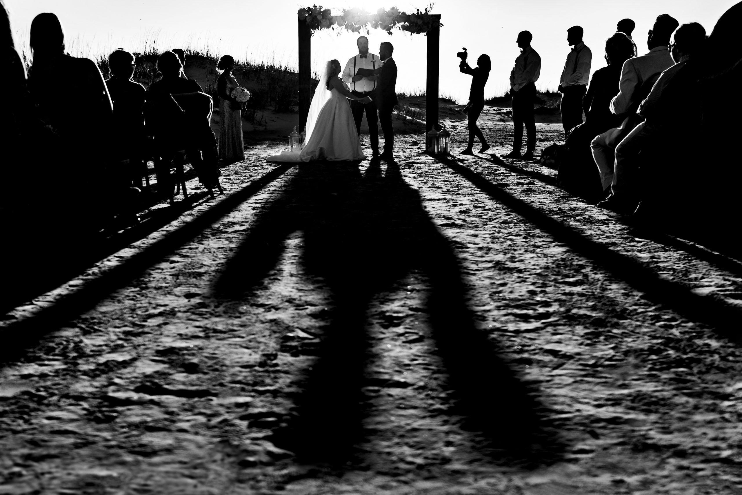 A beach wedding ceremony surrounded by friends and family.