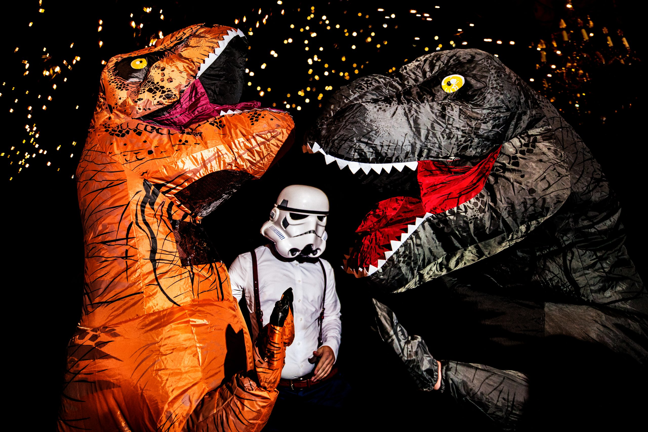 Groom donning a Stormtrooper helmet stands between two friends in inflated dinosaur costumes.