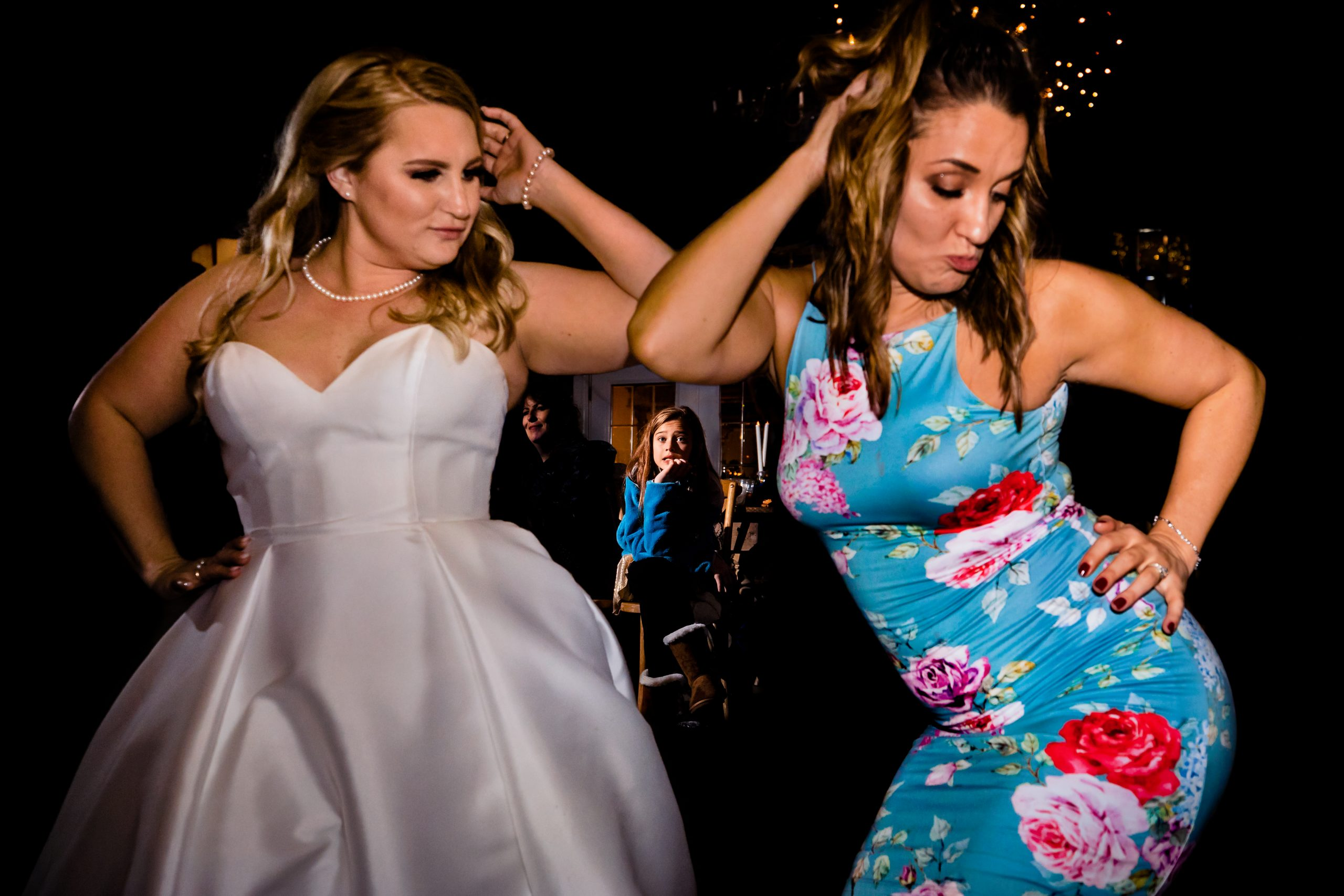 Young girl watches as the bride and her friend work on their dance moves.