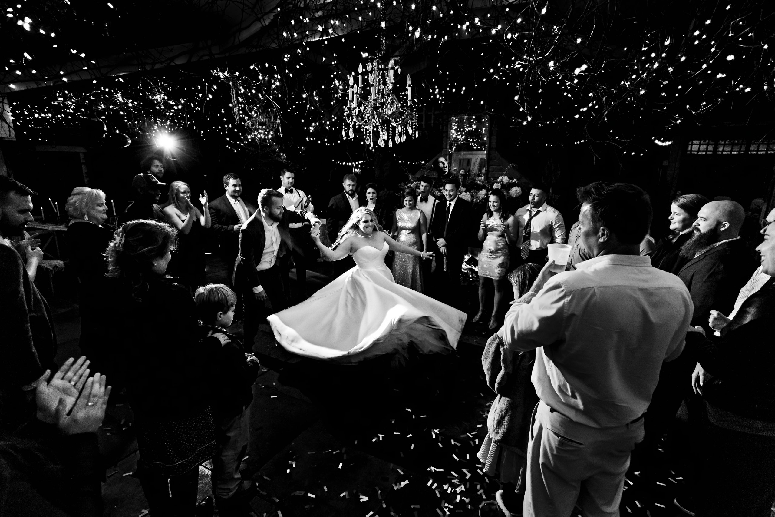 Bride and groom enjoy their first dance among friends and family.