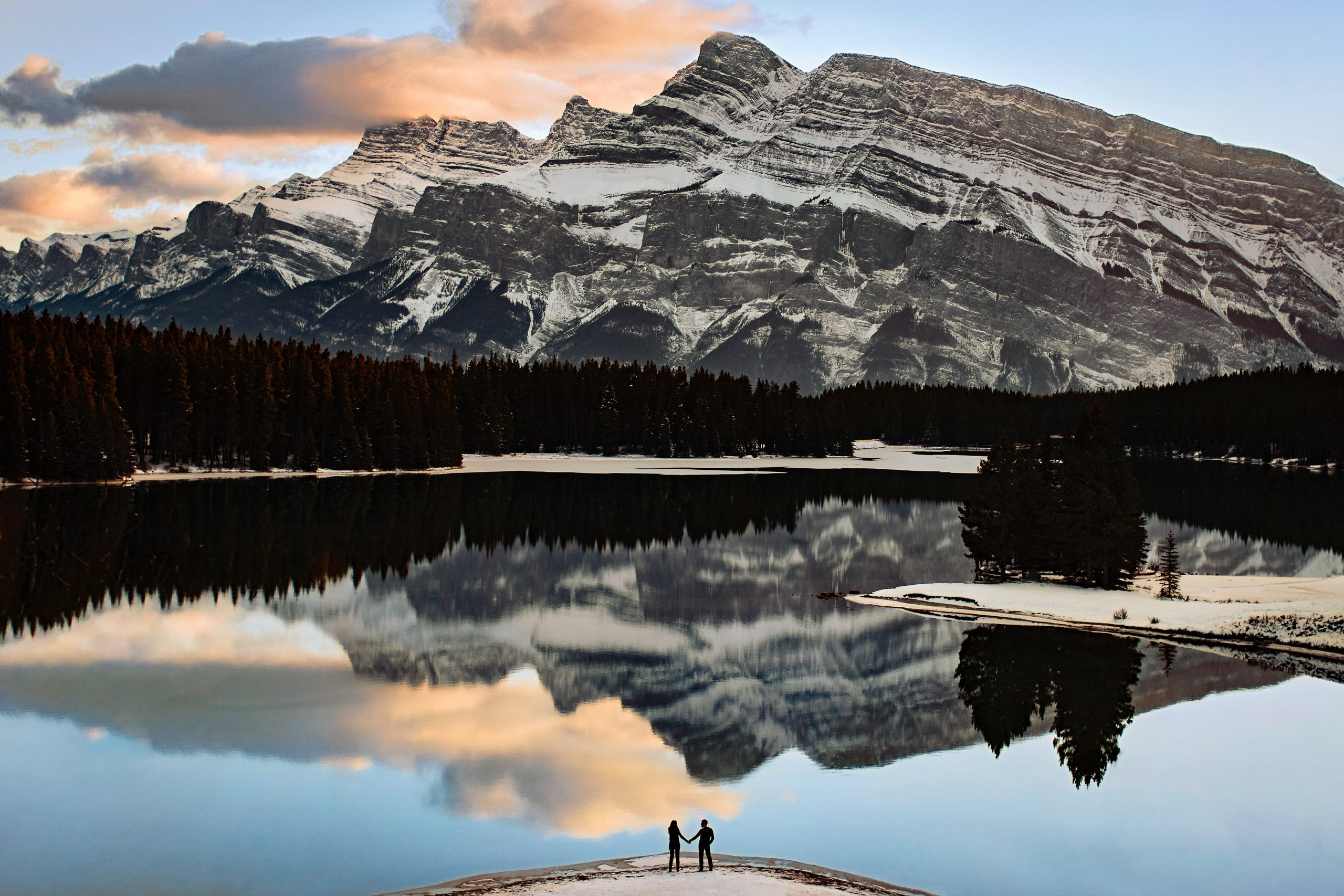 A couple hold hands and look out into a picturesque mountain landscape
