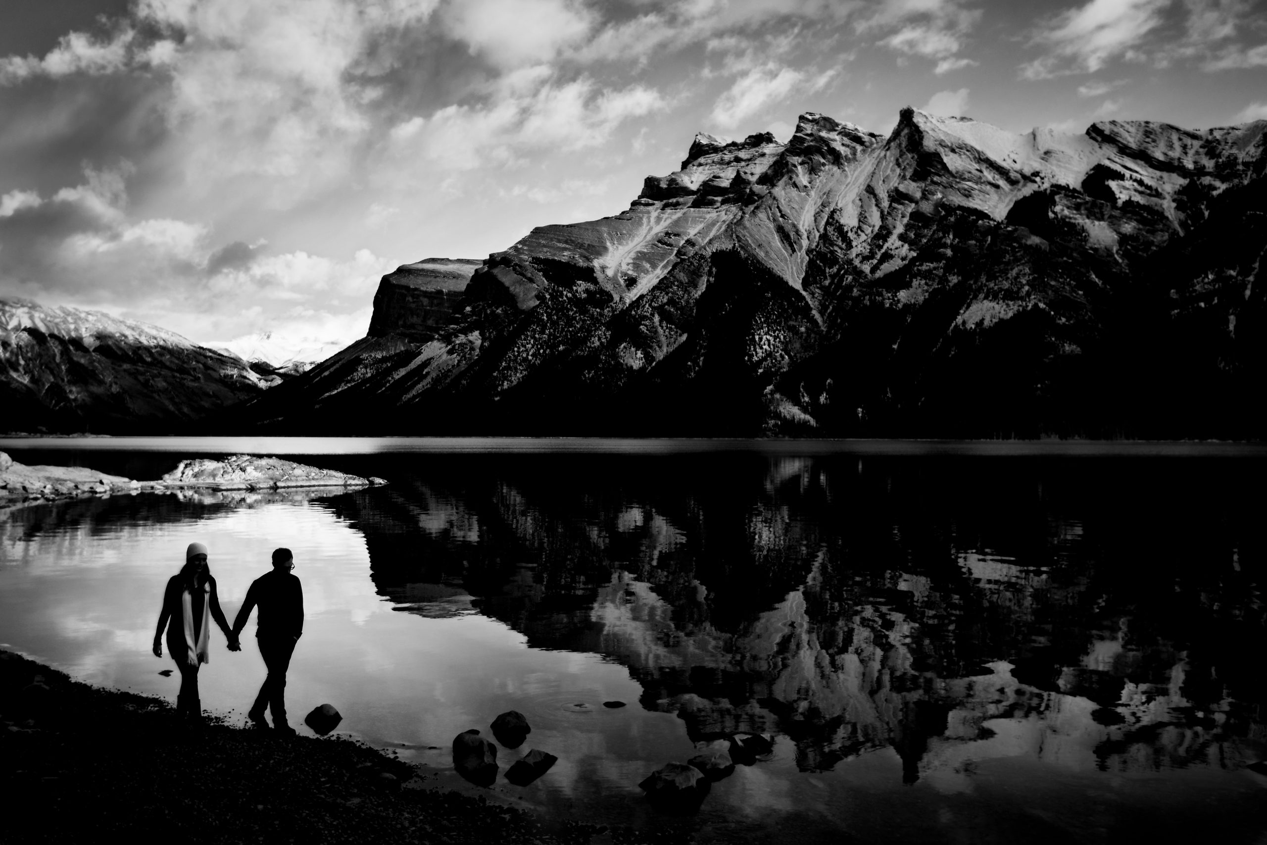 A couple walk along a lake with a clear reflection of the mountain in the background