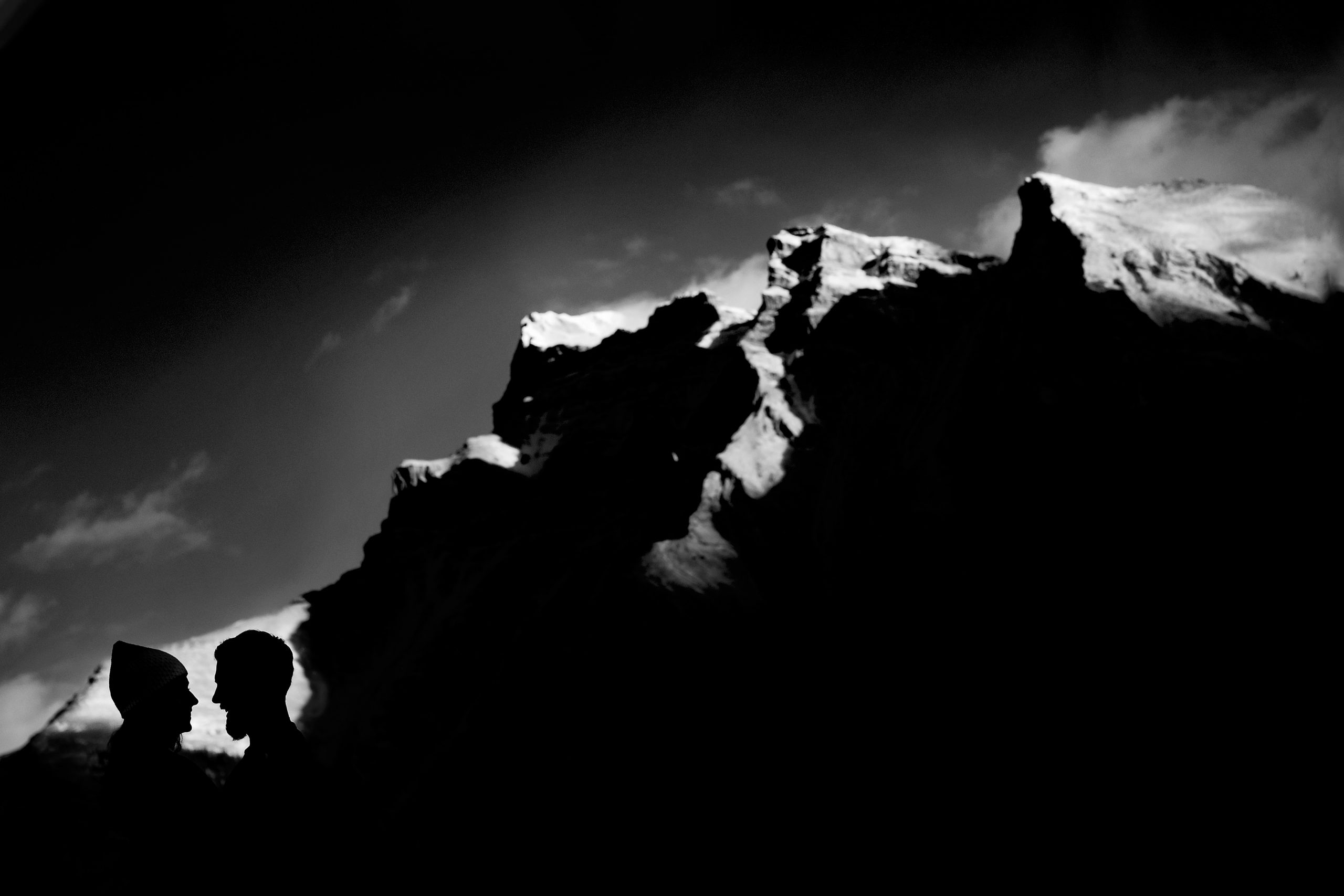 A silhouette of a man and woman look into each other's eyes under the shadow of the Rocky Mountains
