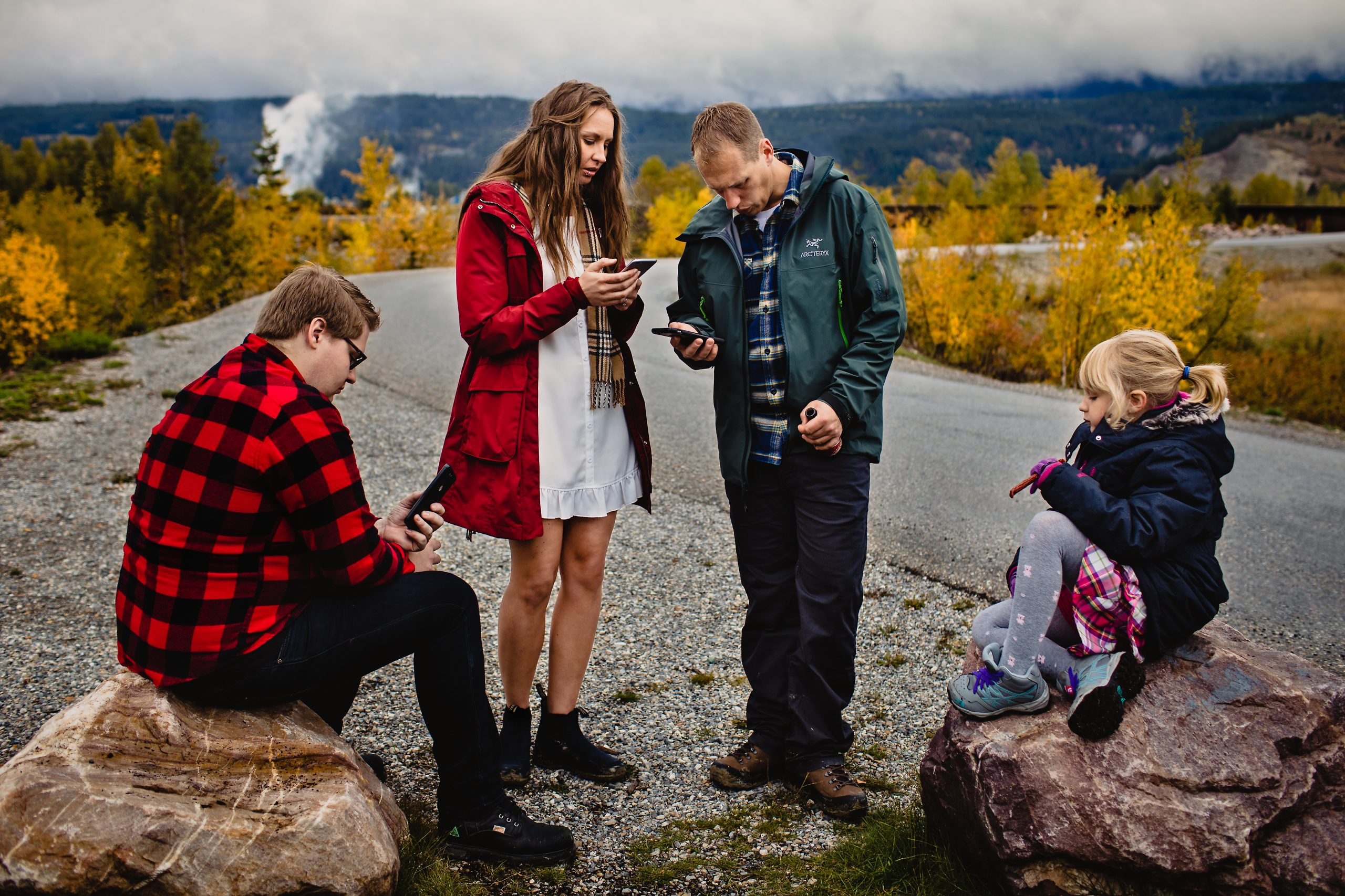 Four people sitting and standing roadside on a fall morning