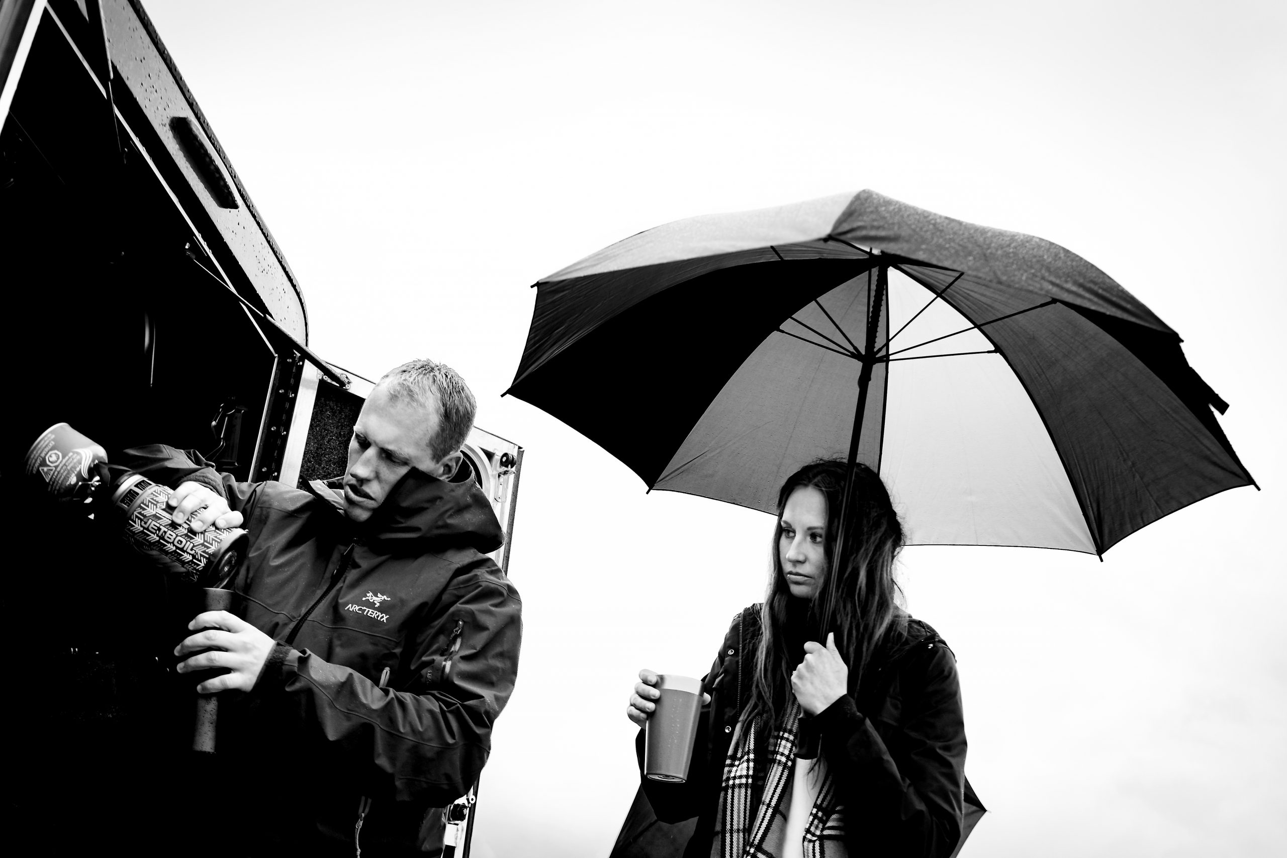 Man pours a coffee while woman stands next to him under an umbrella