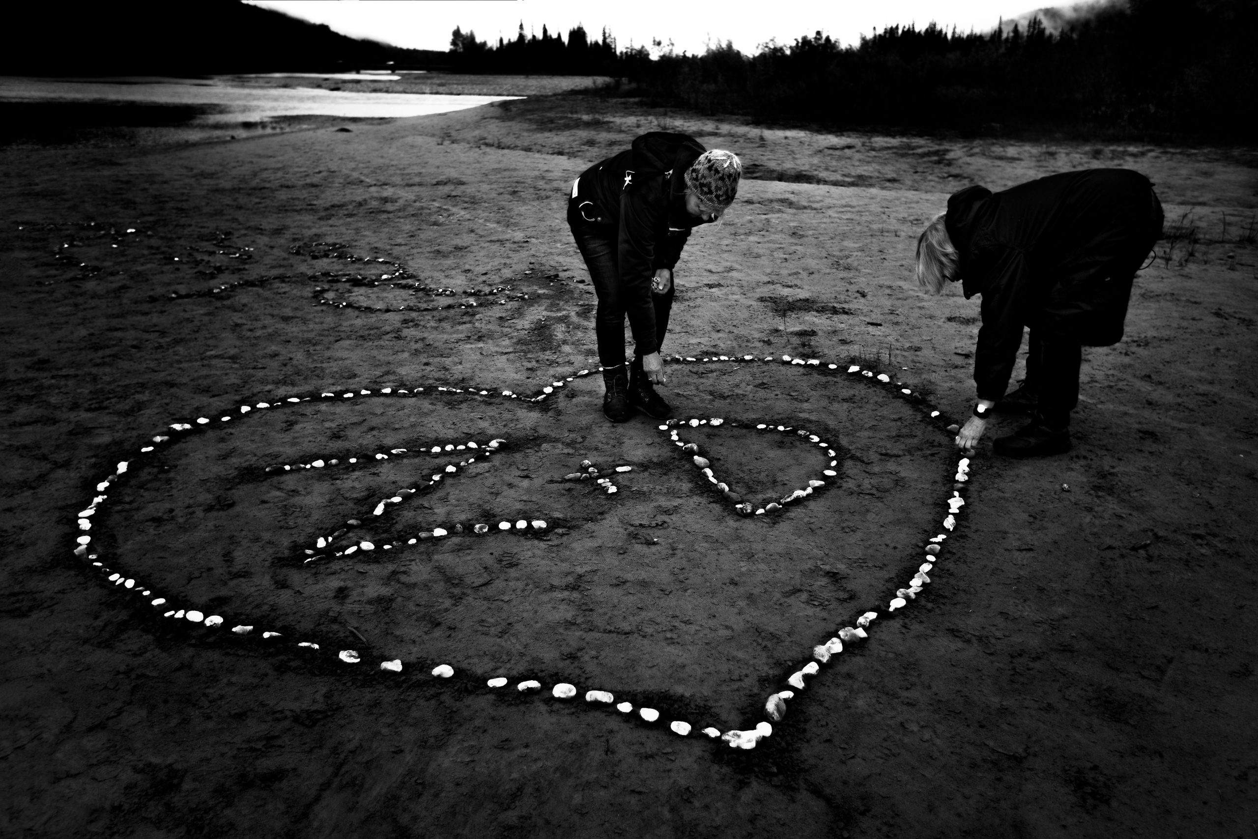 Two woman make a heart with the initials of Z and D out of rocks