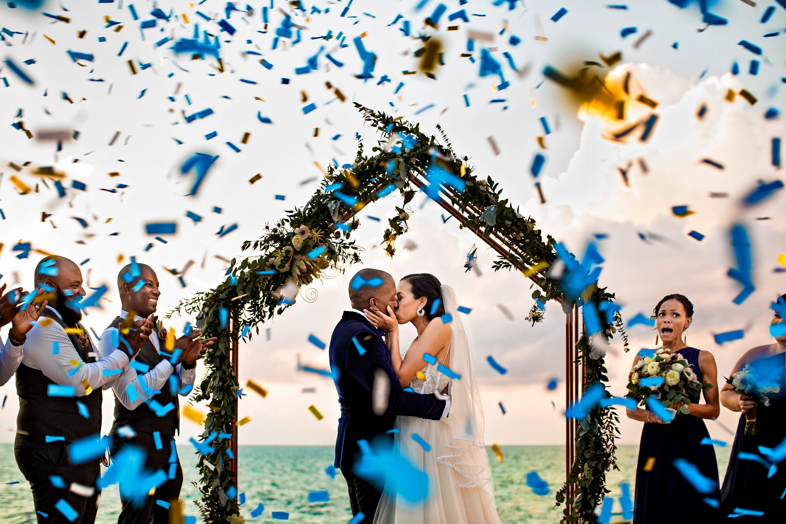 Confetti and emotions fly during a bride and groom's first kiss at a seaside ceremony.