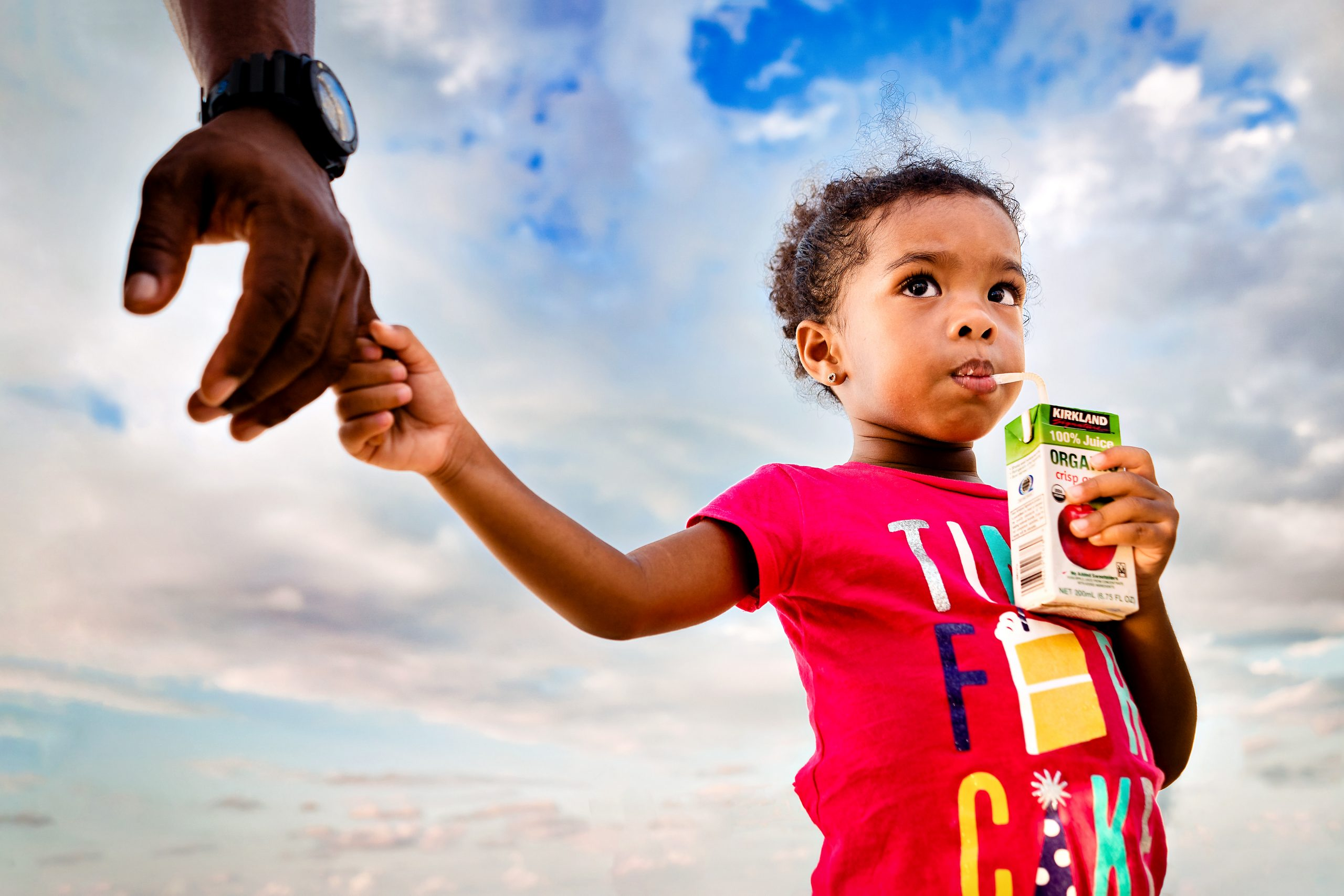 Young girl holds dad's hand and drinks from a juice box.