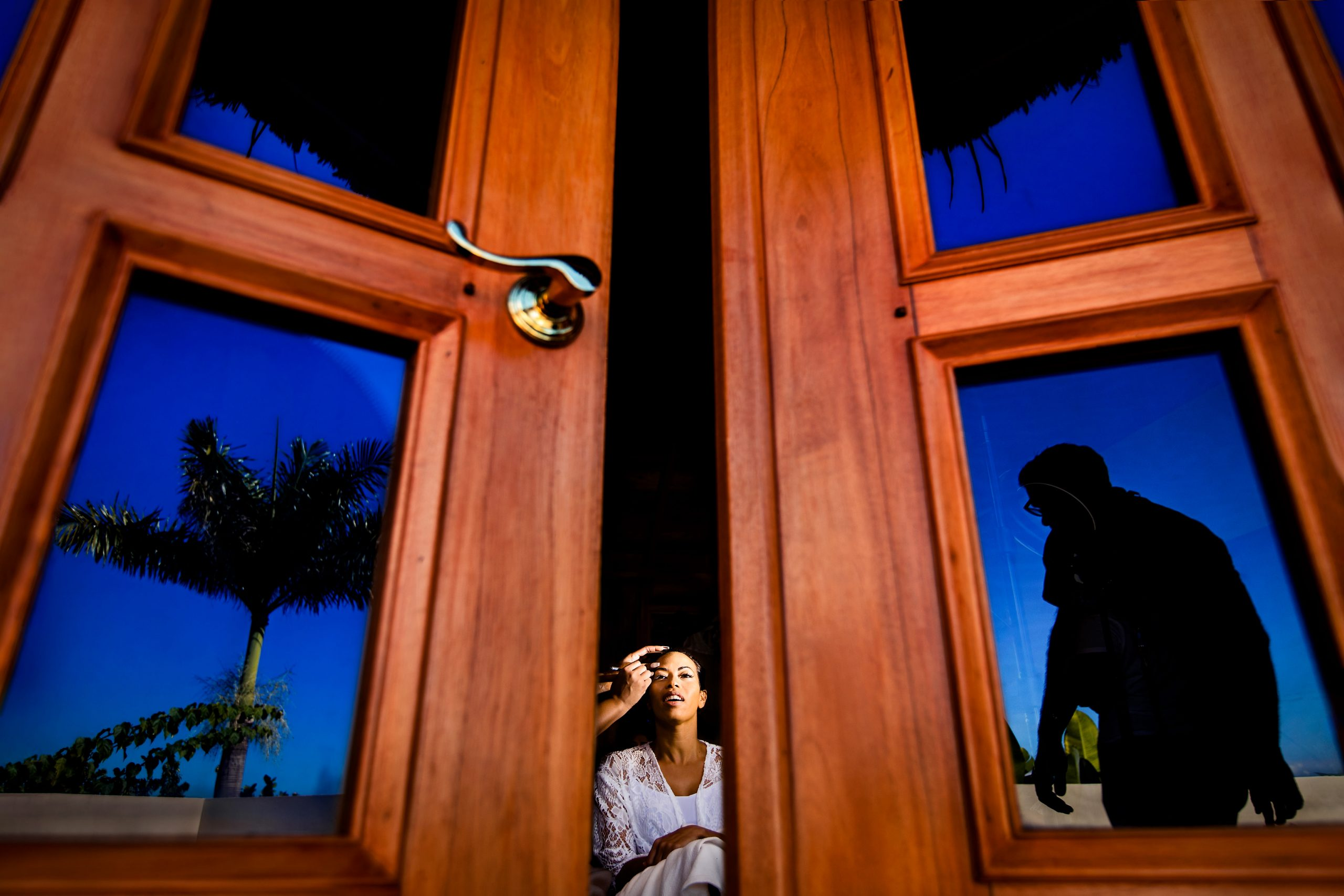 Groom getting her makeup done is seen in the crack of a pair of wooden doors.