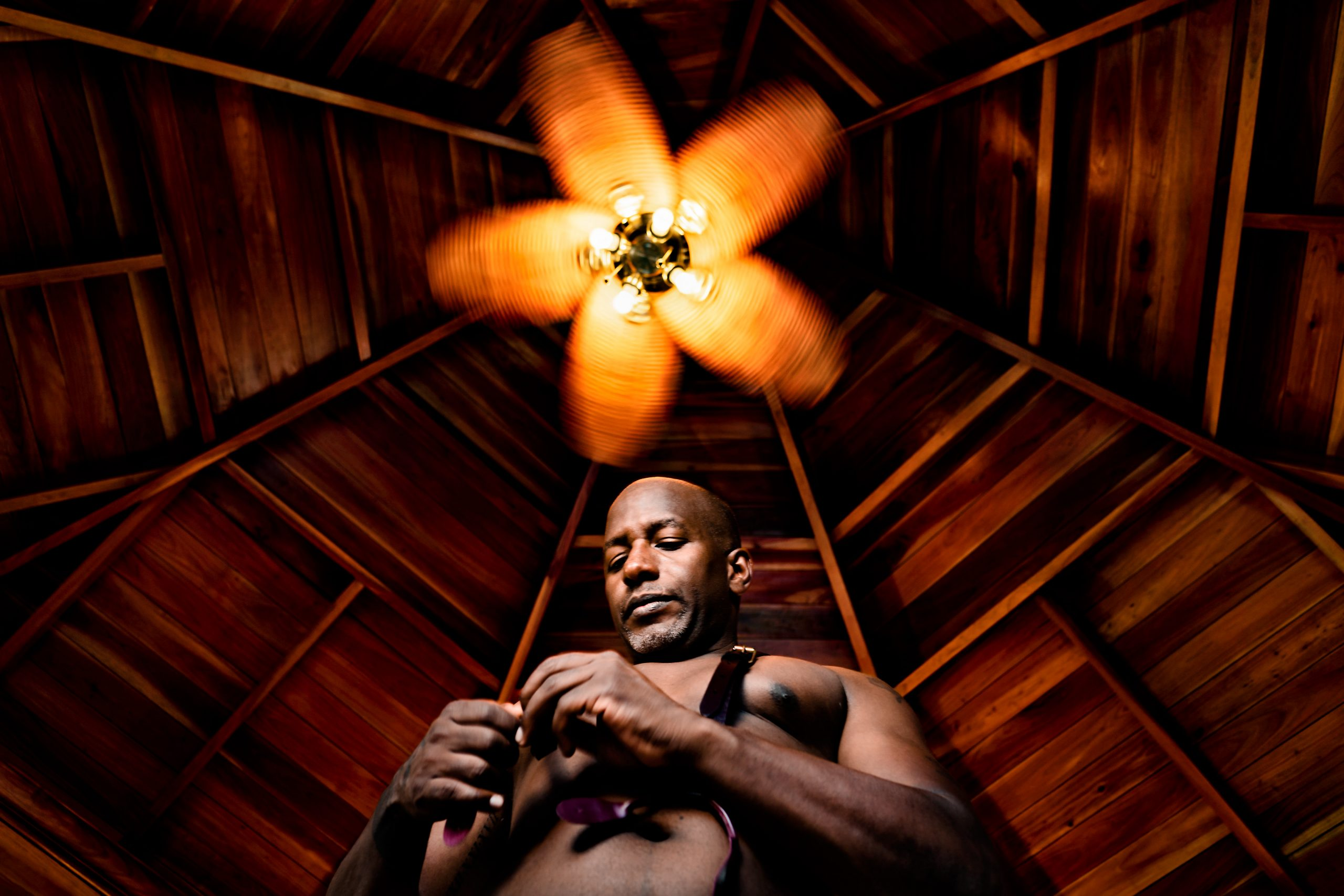 Man gets dressed to the backdrop of a wooden ceiling fan.