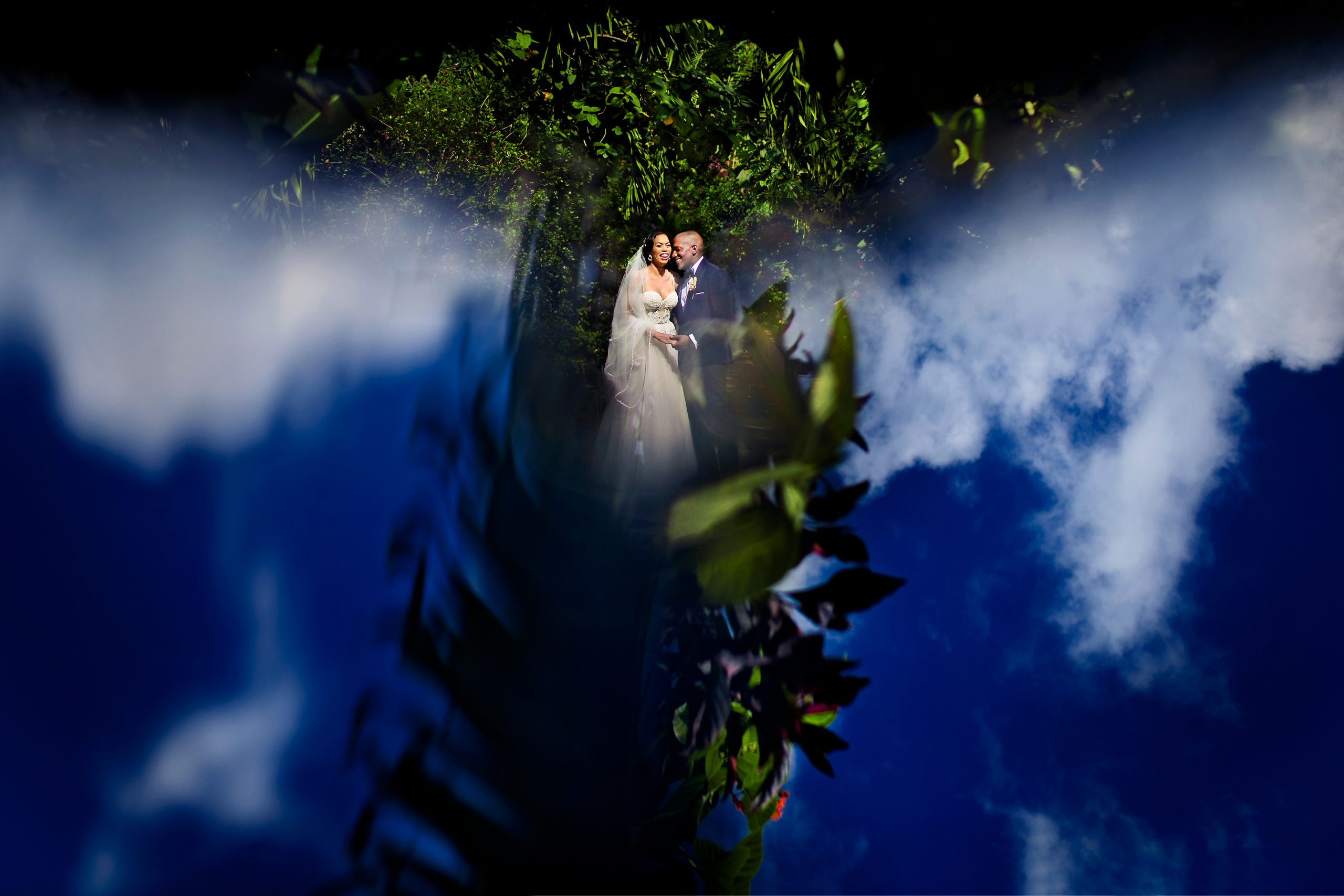 Reflection of the sky surrounds the newly wed couple.