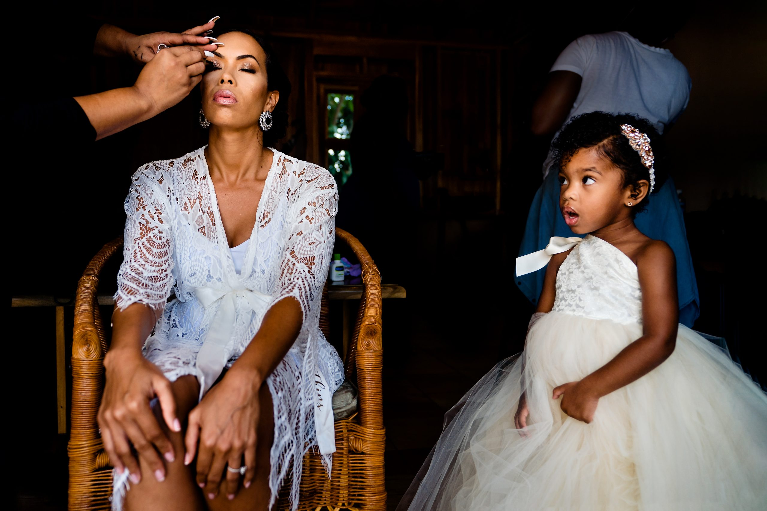 Dressing in white, a young girl watches wedding makeup get applied to the bride.