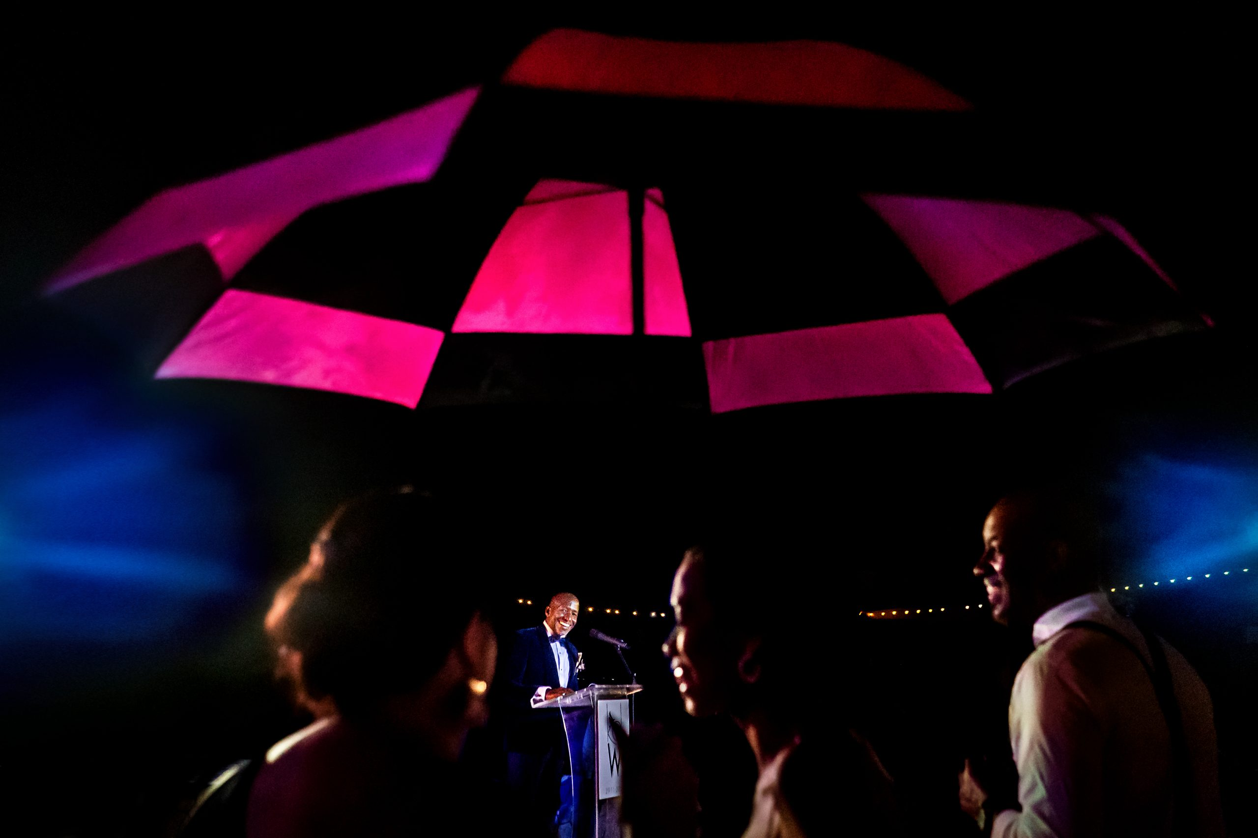 A wedding reception and speech under an umbrella.