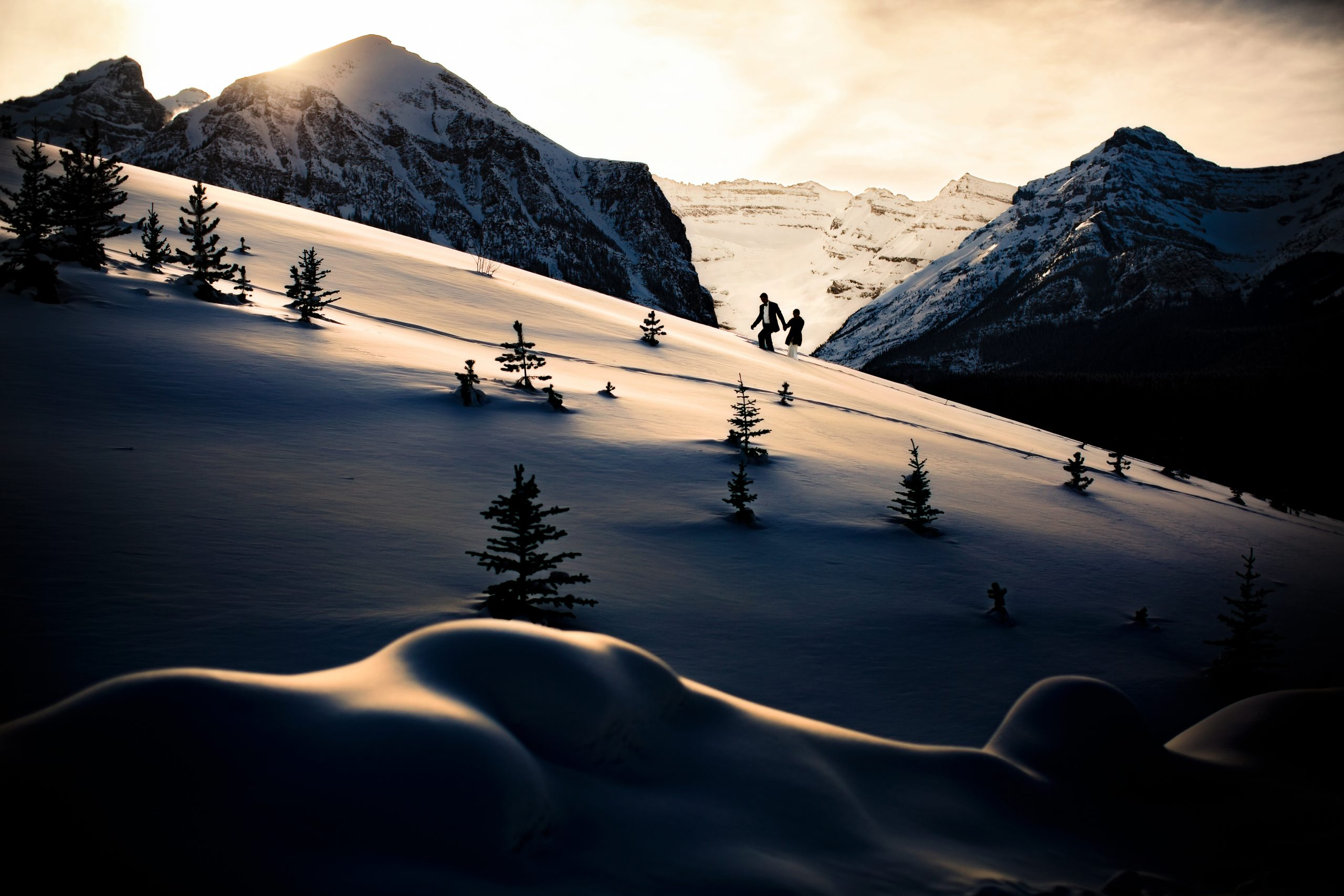A couple walk among the mountains on a frosty winter morning.