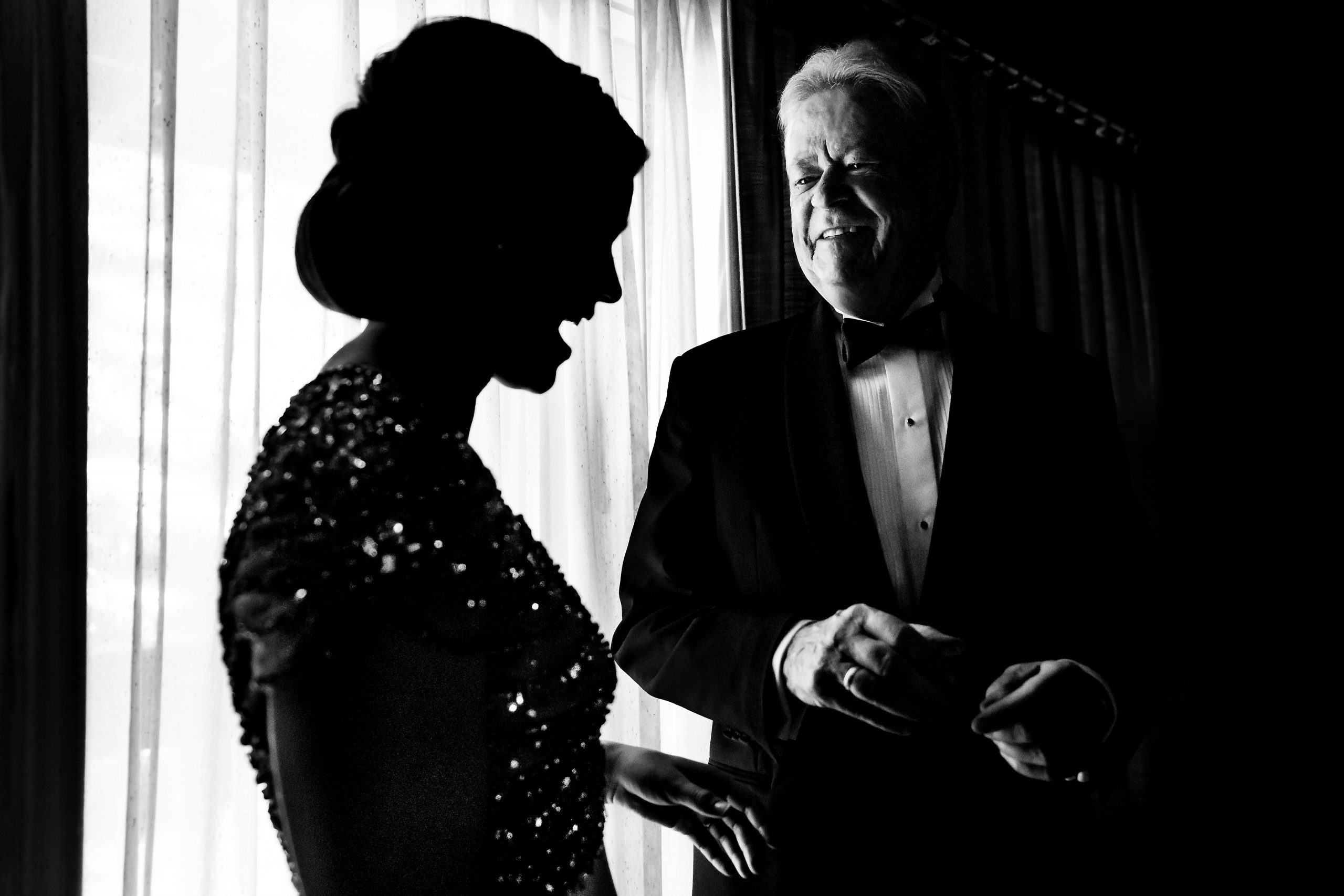 A proud father talks with the bride who is silhouetted by the light outside of the room.