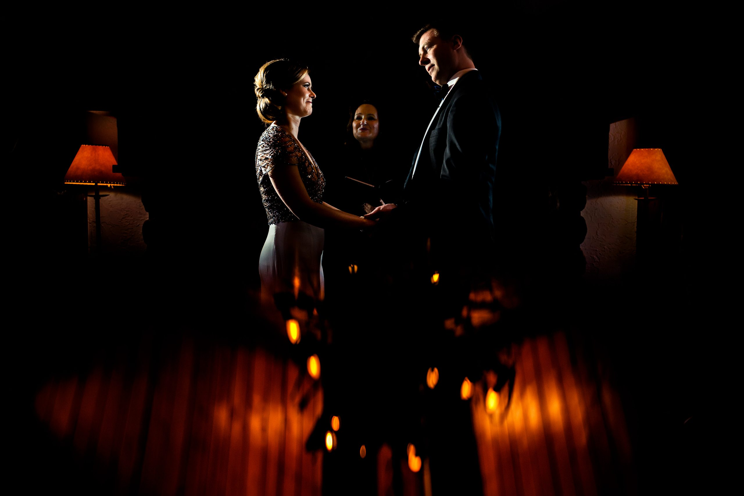 Bride and groom's wedding ceremony illuminated by warm lamps.