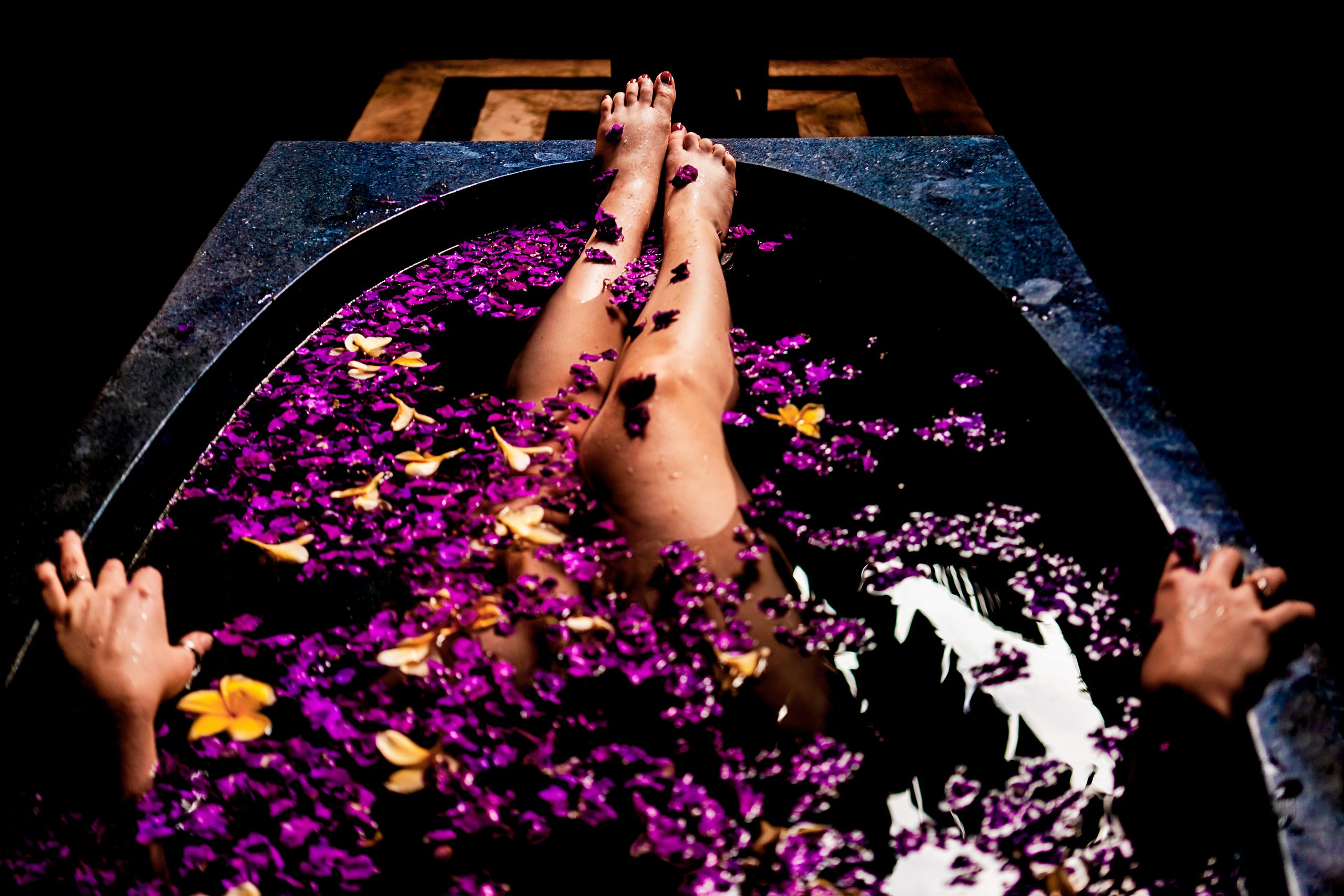 Woman sticks her legs out of a bathtub filled with flowers