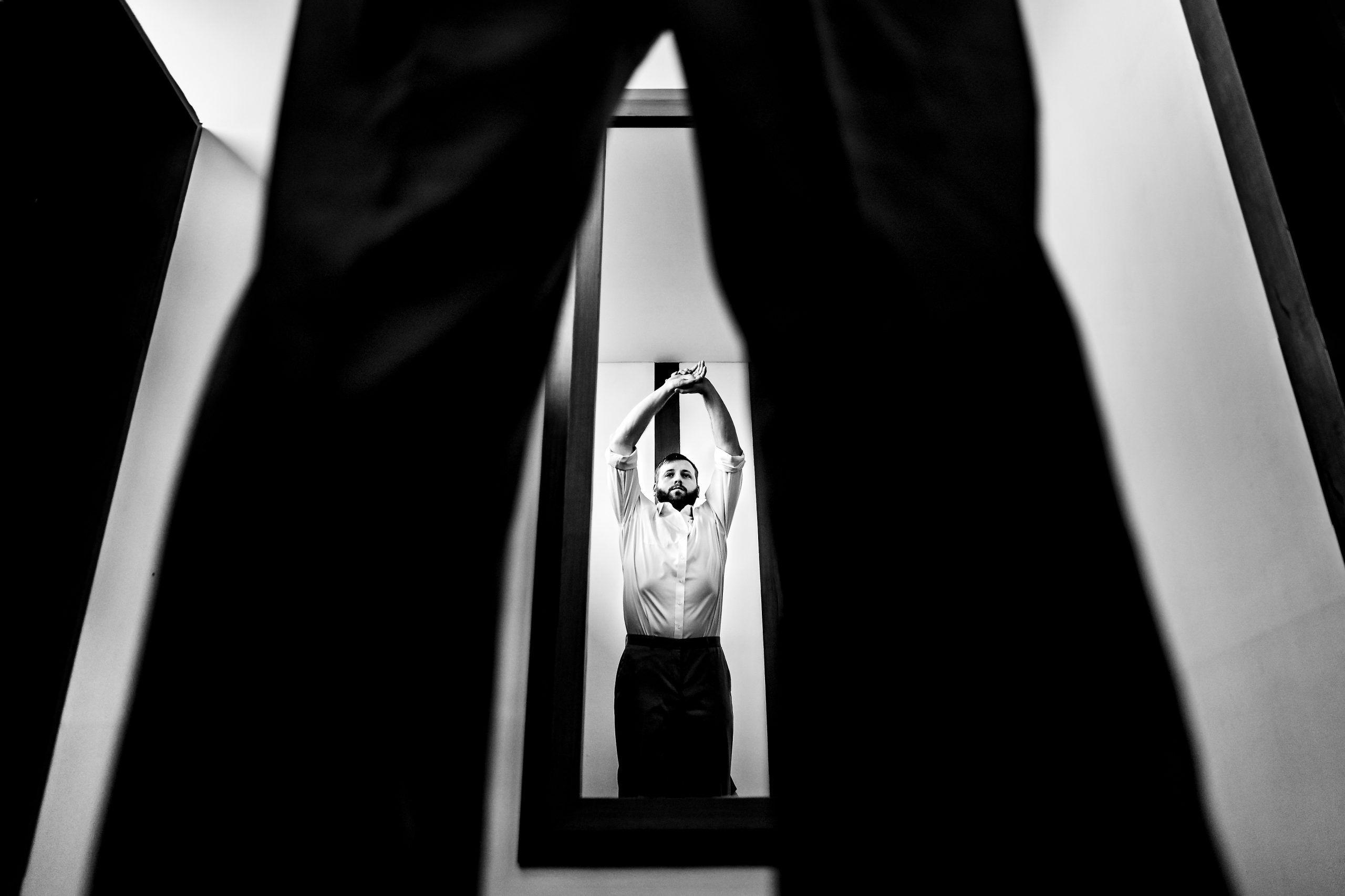 Man stretches in front of a mirror