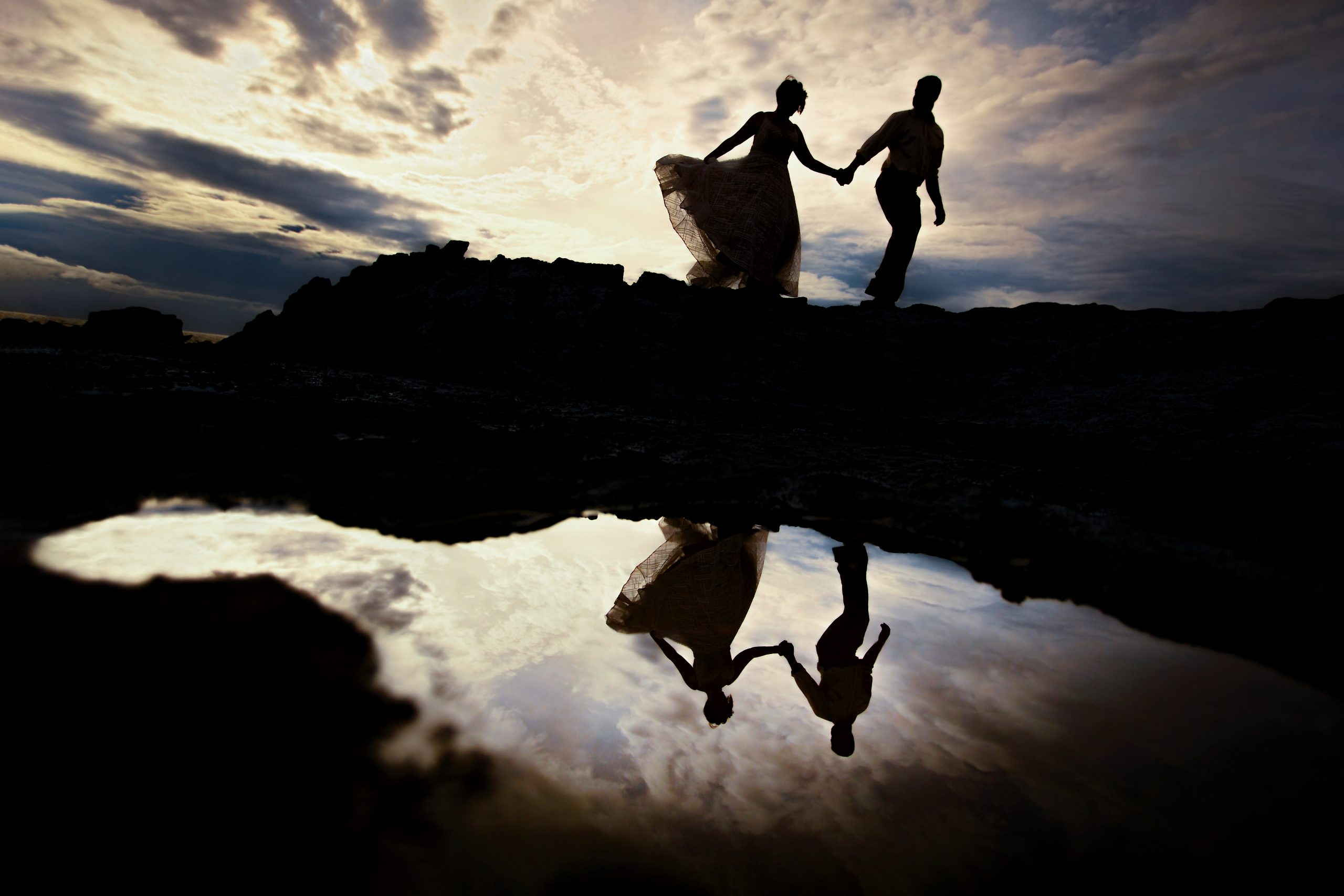 Silhouette of a couple walking hand in hand by the sea with reflection on the ground