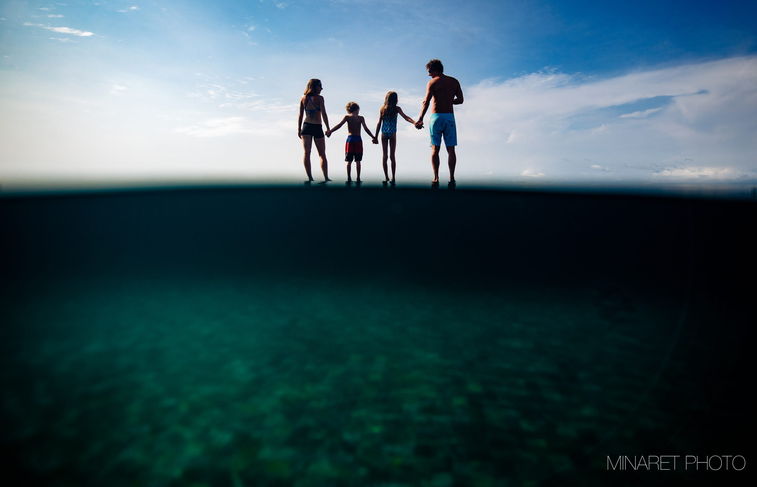 A couple with their son and daughter stand hand in hand between water and sky