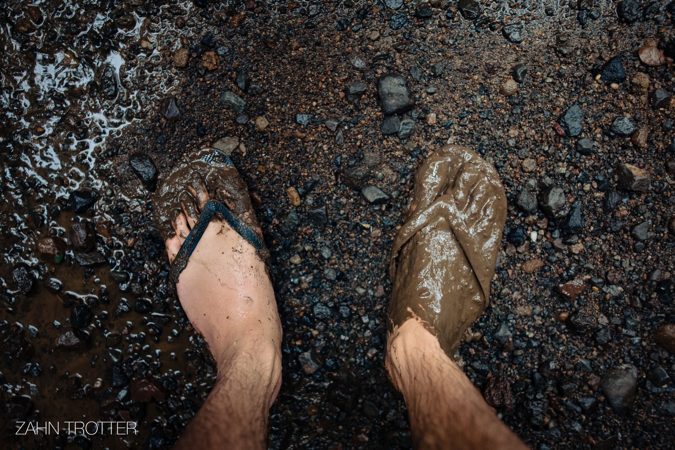 A man's muddy feet and flip flops