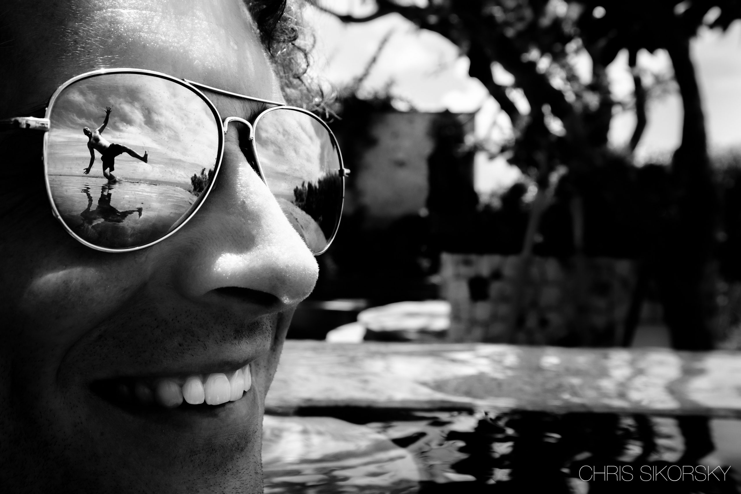 Reflection of a man jumping into the water is seen on a man's sunglasses