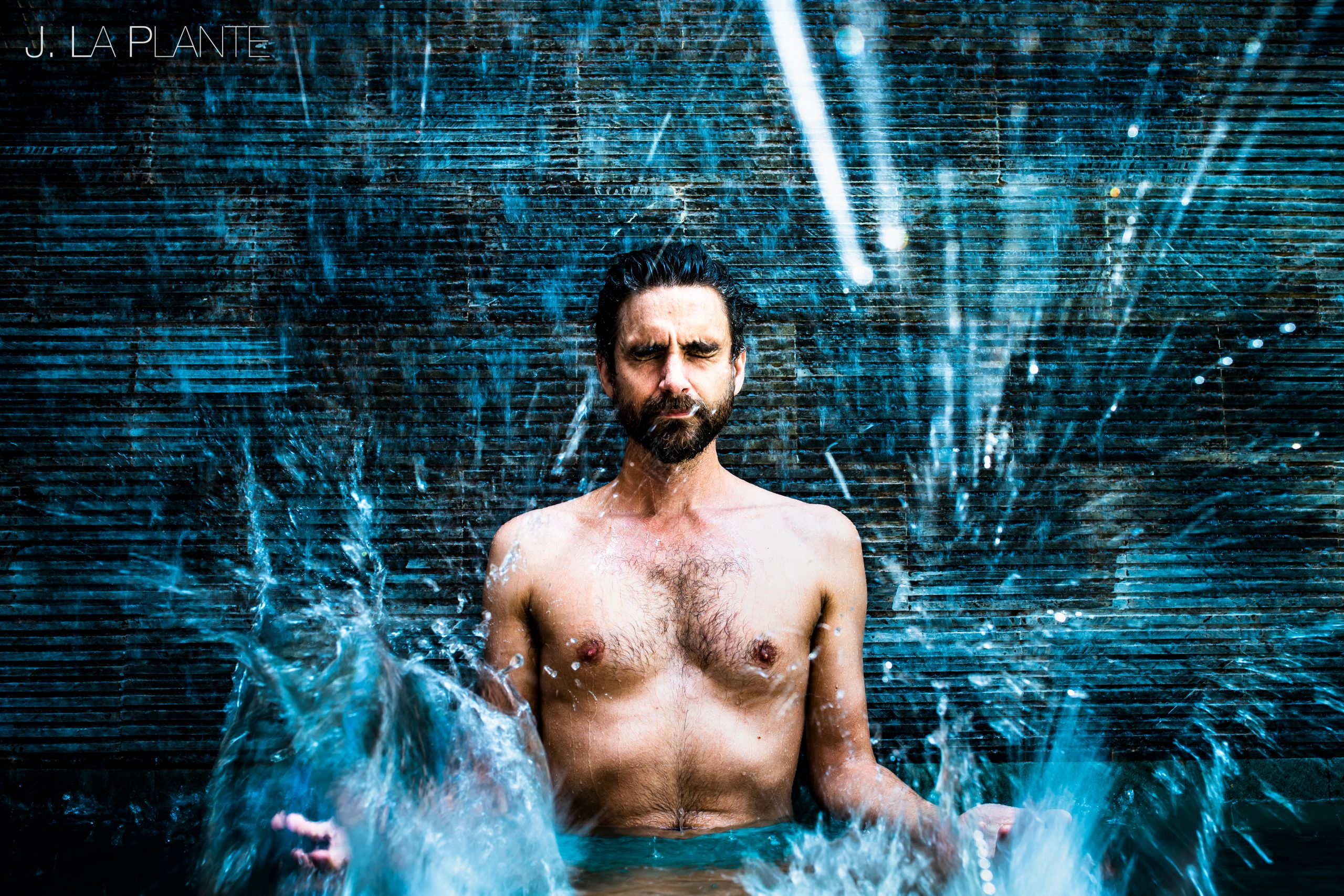 Man takes a meditative pose among the chaos of splashing water