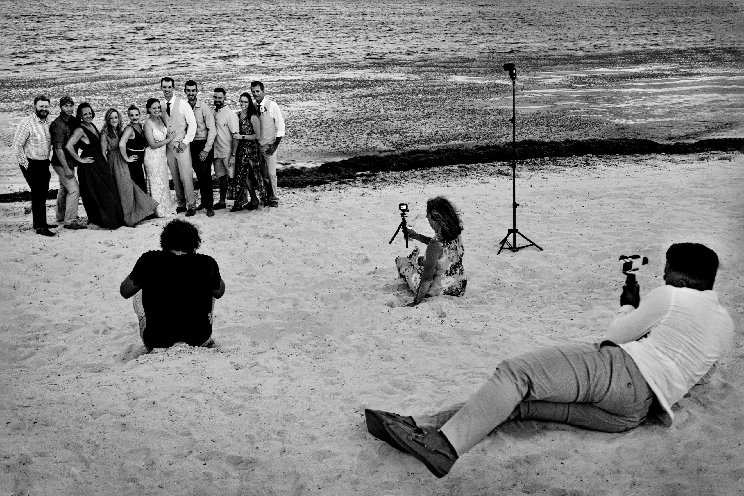 Photographers and videographers lay beachside to capture a group wedding photo