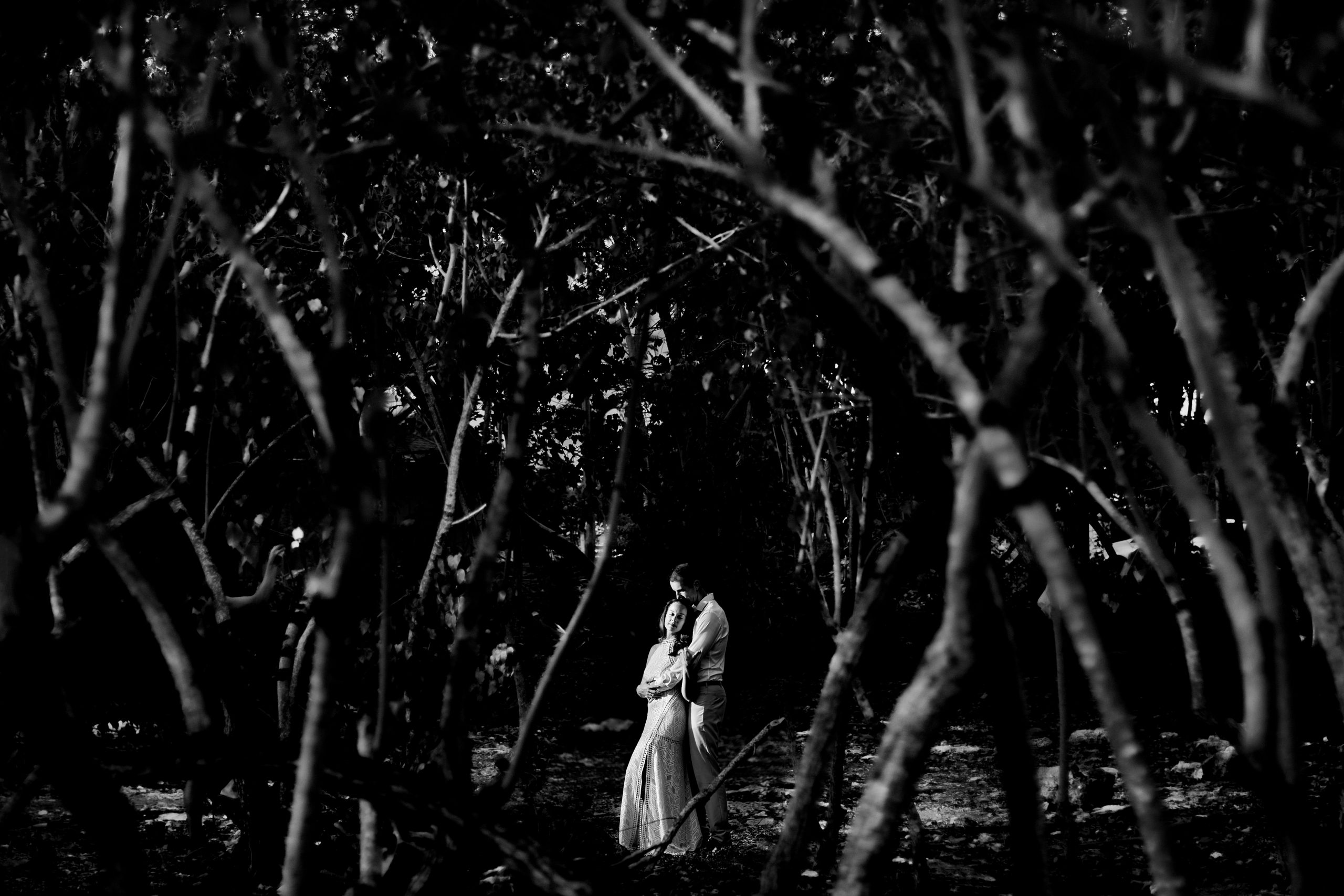 A groom embraces bride in a tropical forest at night