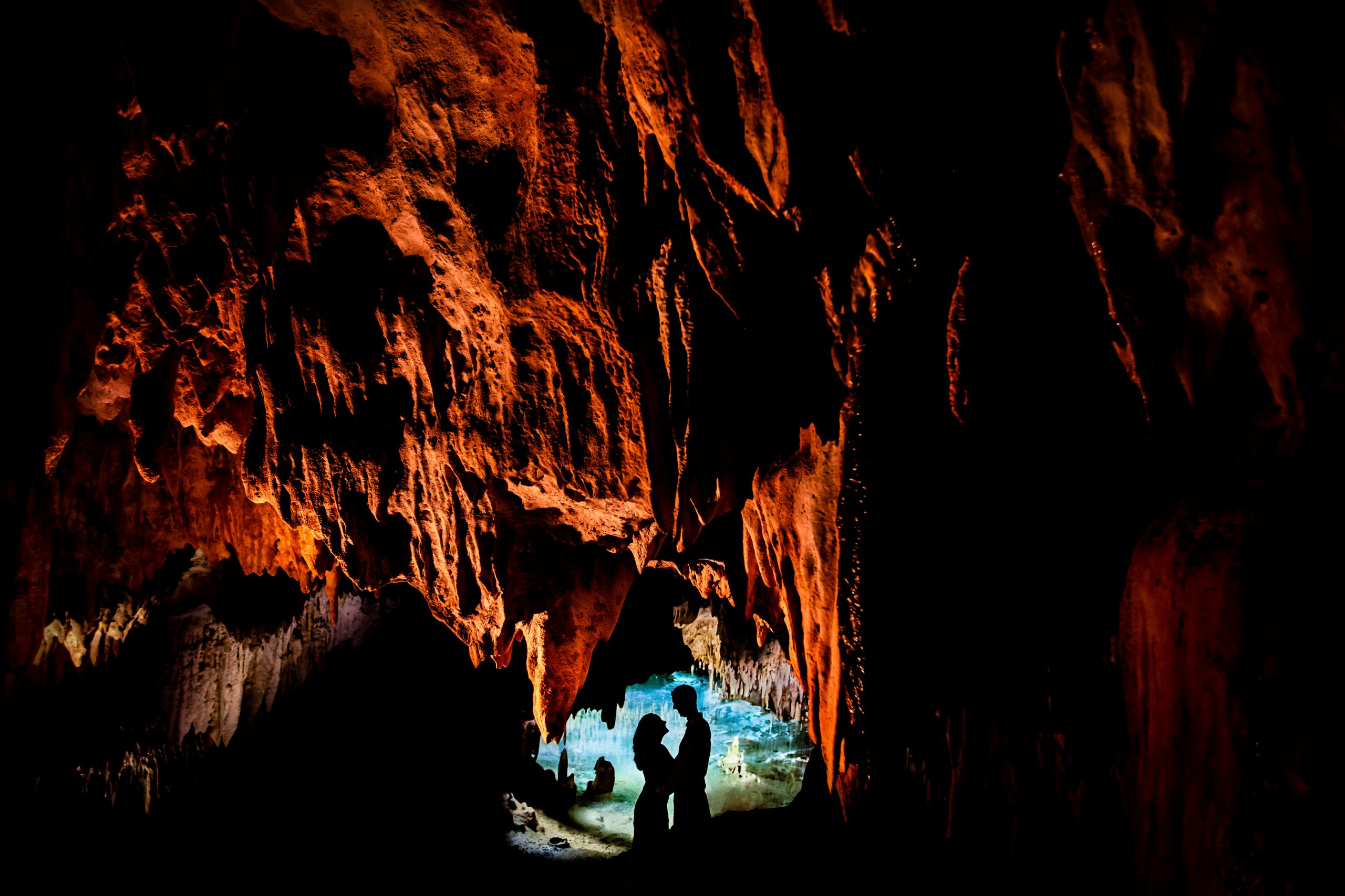 Silhouette of newlyweds embracing each other at the entrance of a cave
