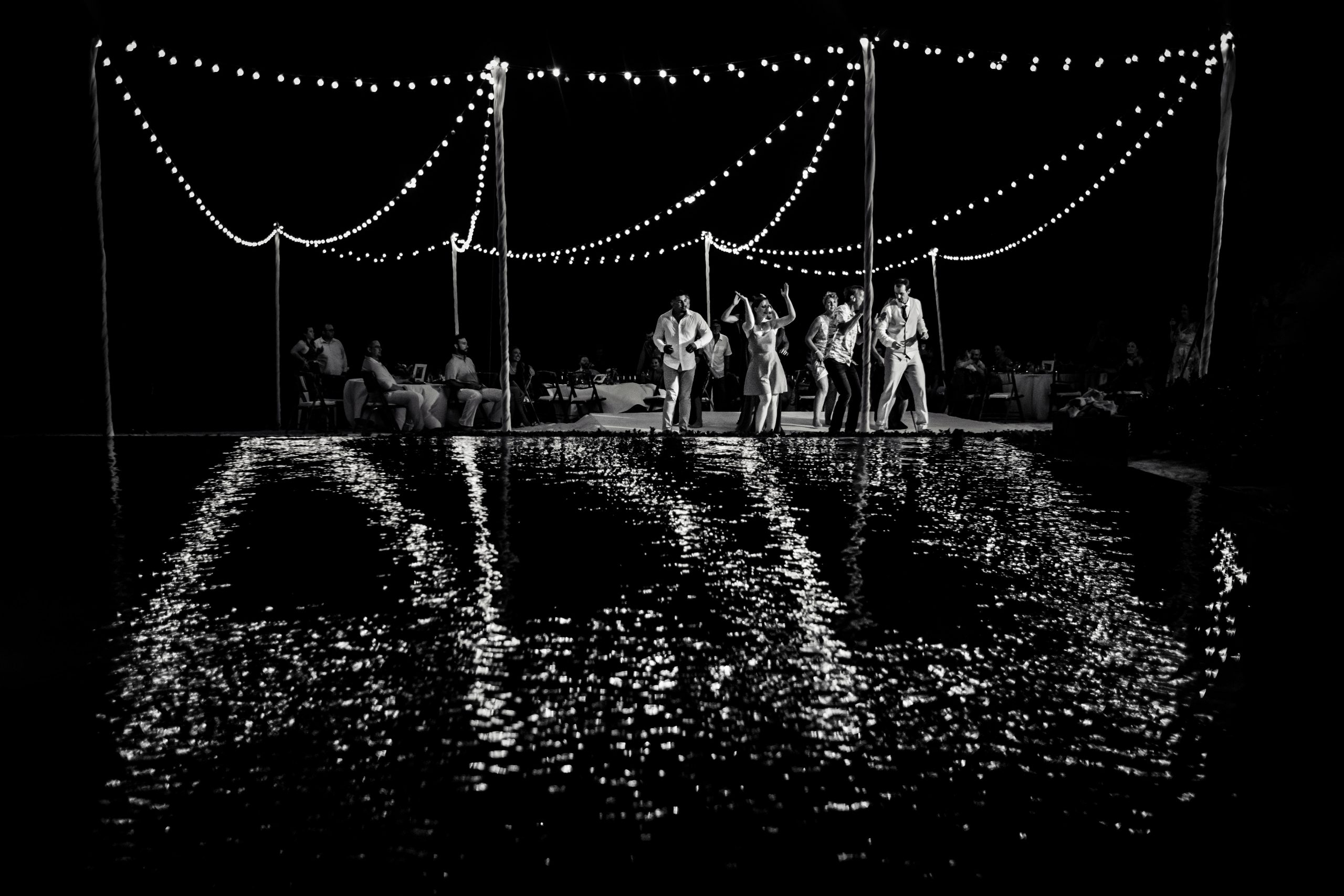 Wedding guests hit the dance floor amidst sparkling lights and reflections in water