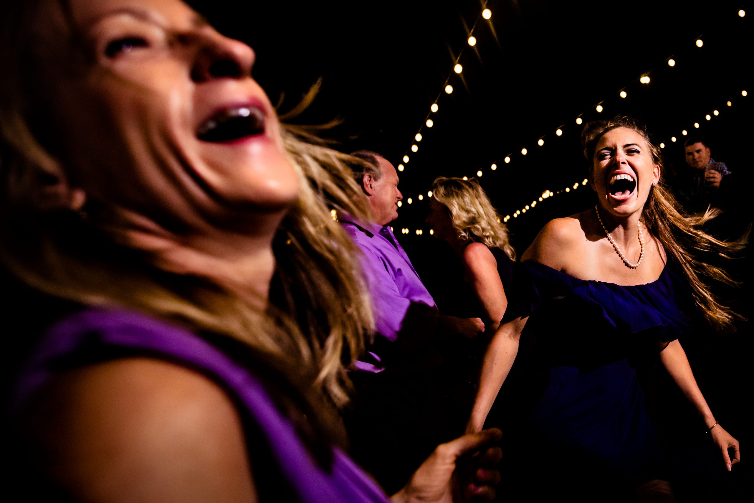 Wedding guests dance happily at a wedding reception party