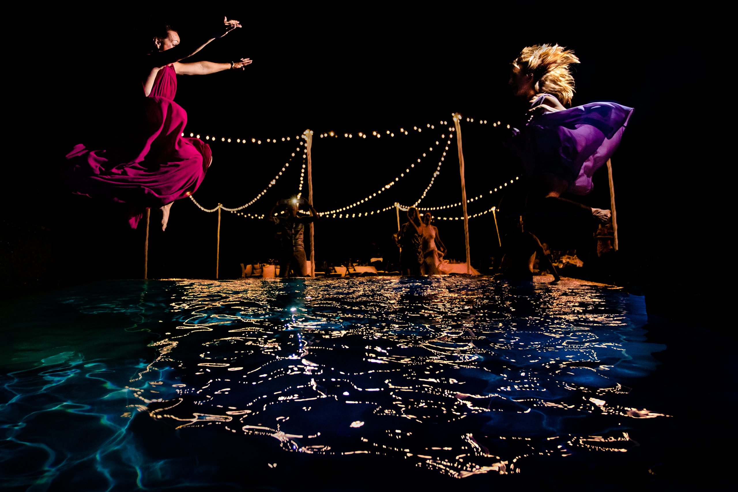 Wedding guests jumping into the pool at reception party