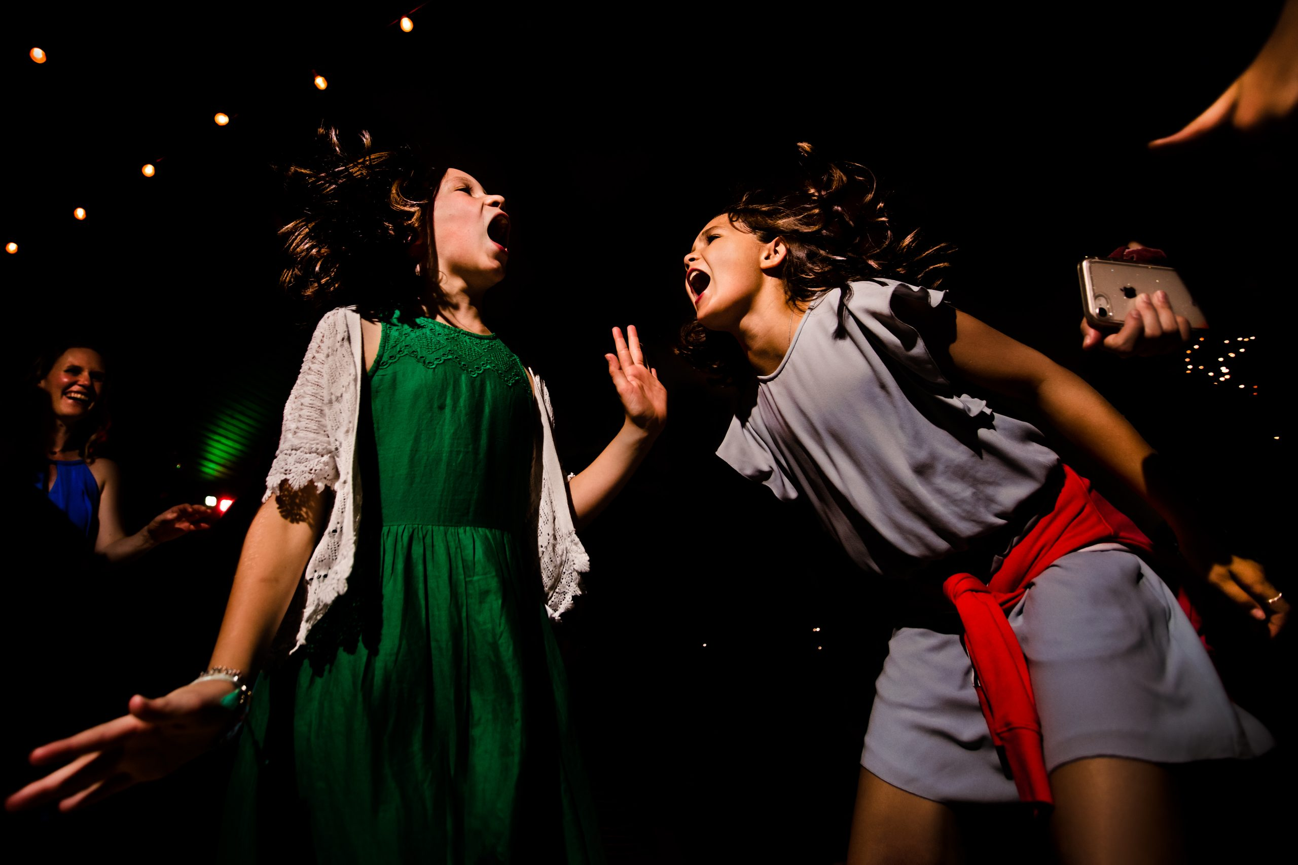 Two girls dance excitedly at a wedding reception party
