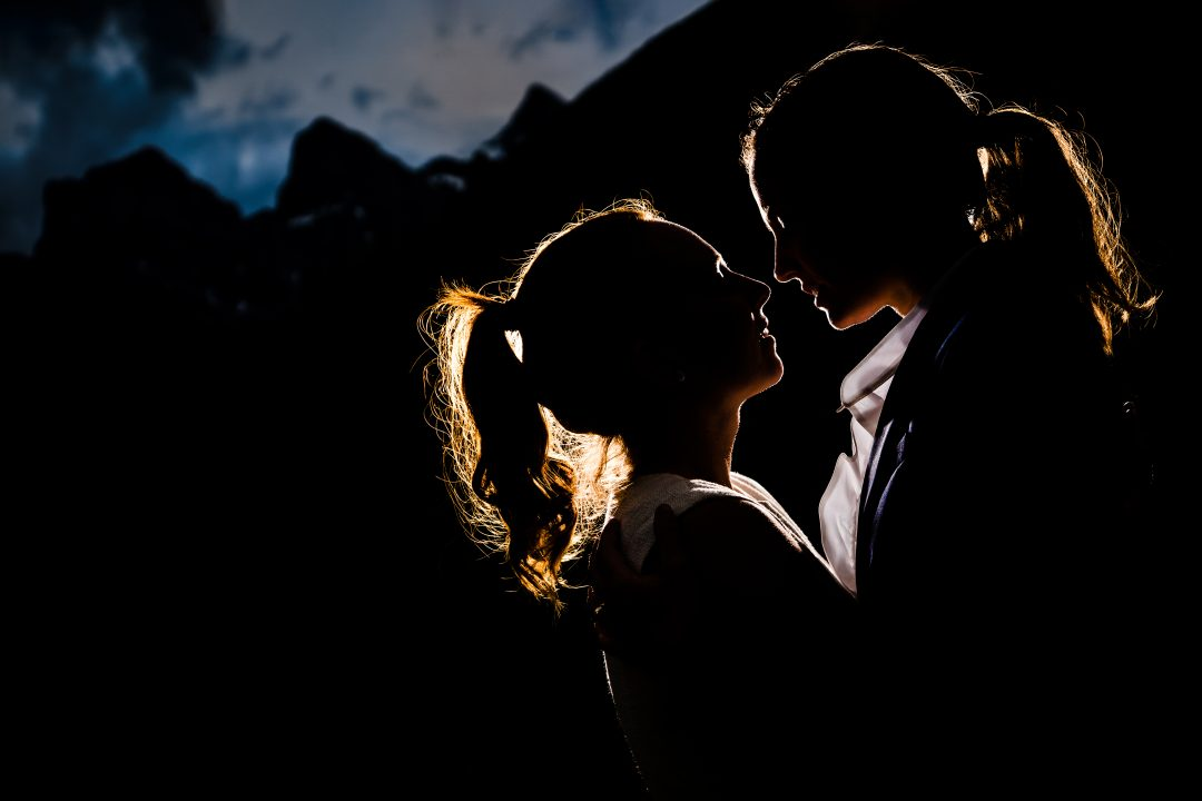 Silhouette of wedding couple holding and looking at each other with background of mountains