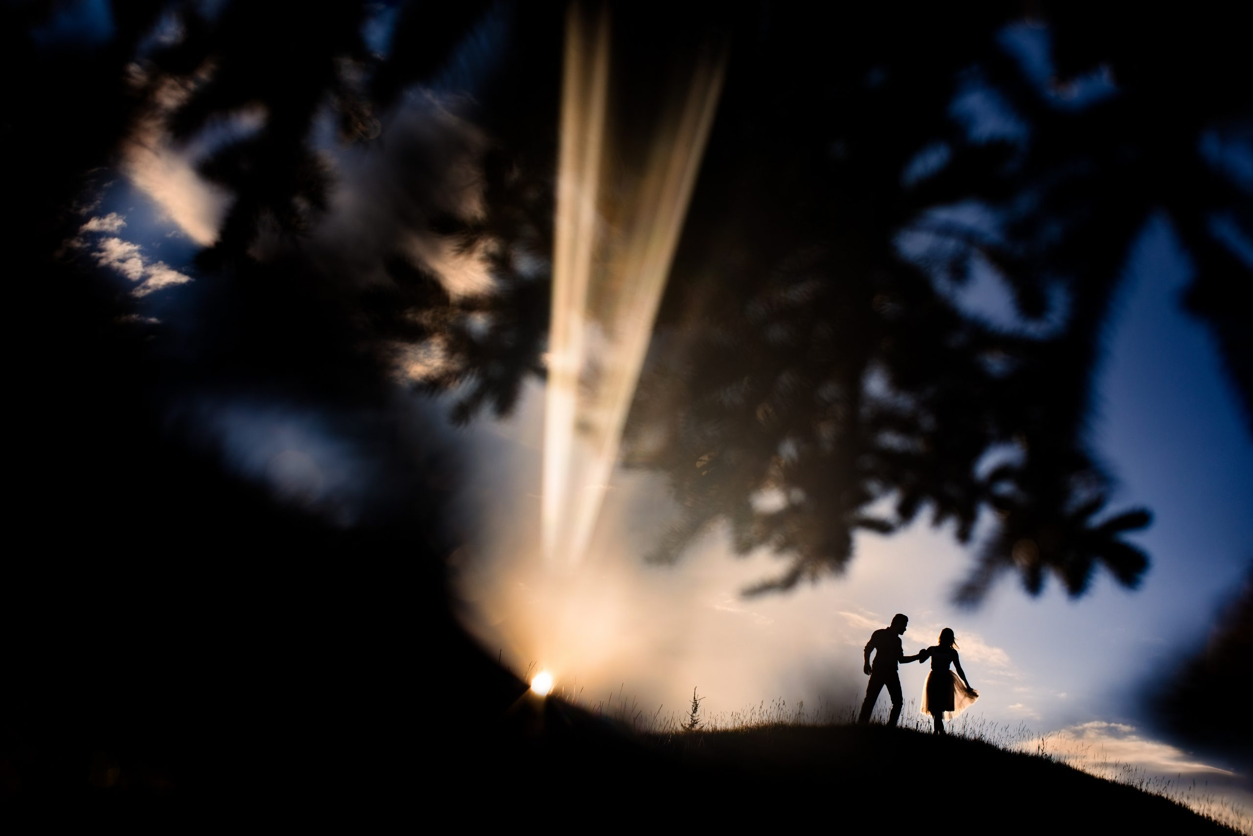 Silhouetted couple hold hands as rays of dawn shine through.