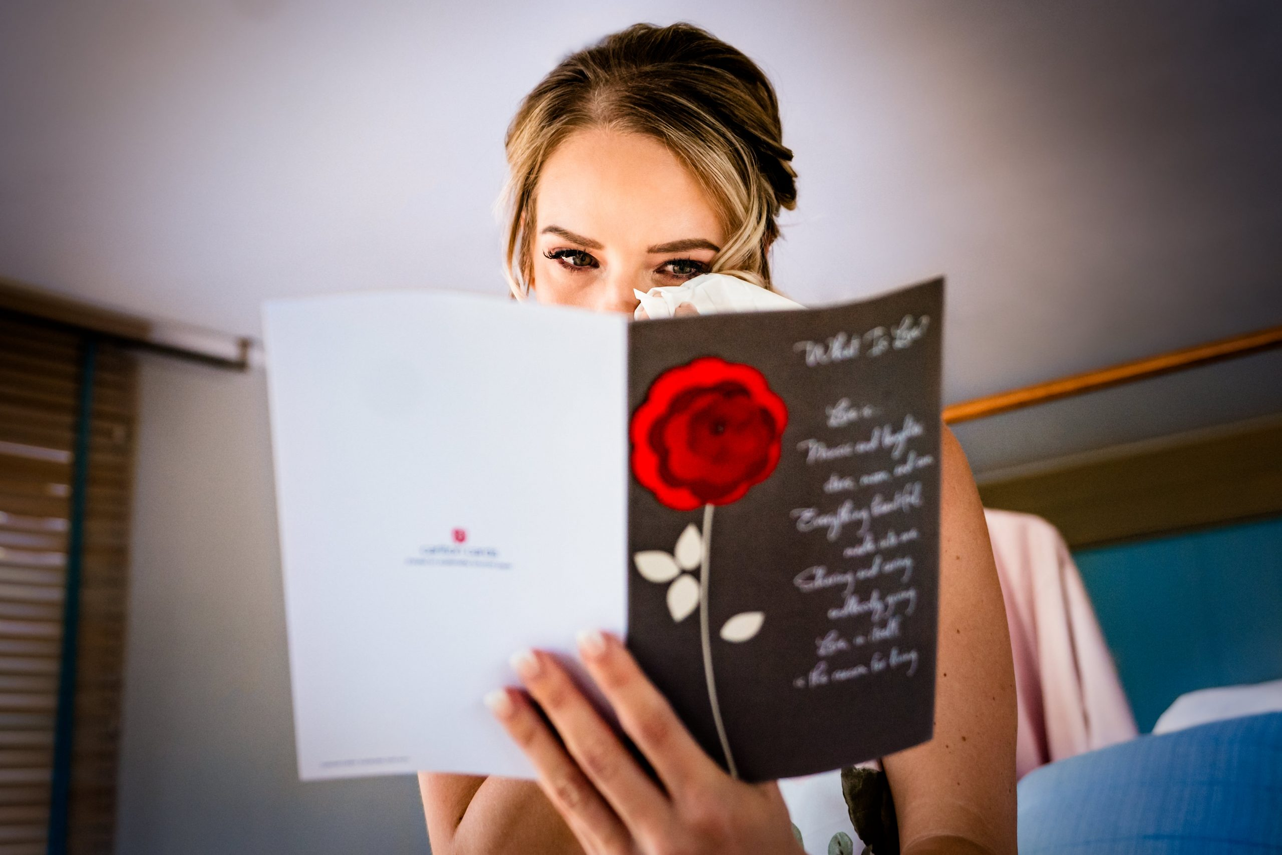 Bride wipes away tears while reading a congratulatory card.