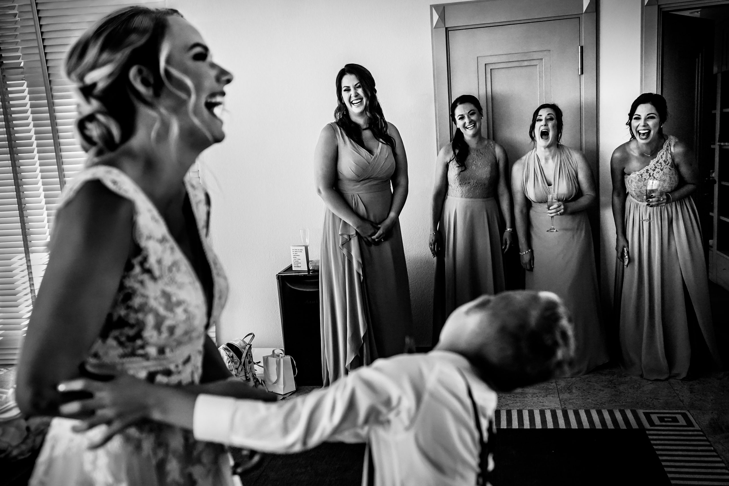 Boy dances with his mother as bridesmaids laugh.