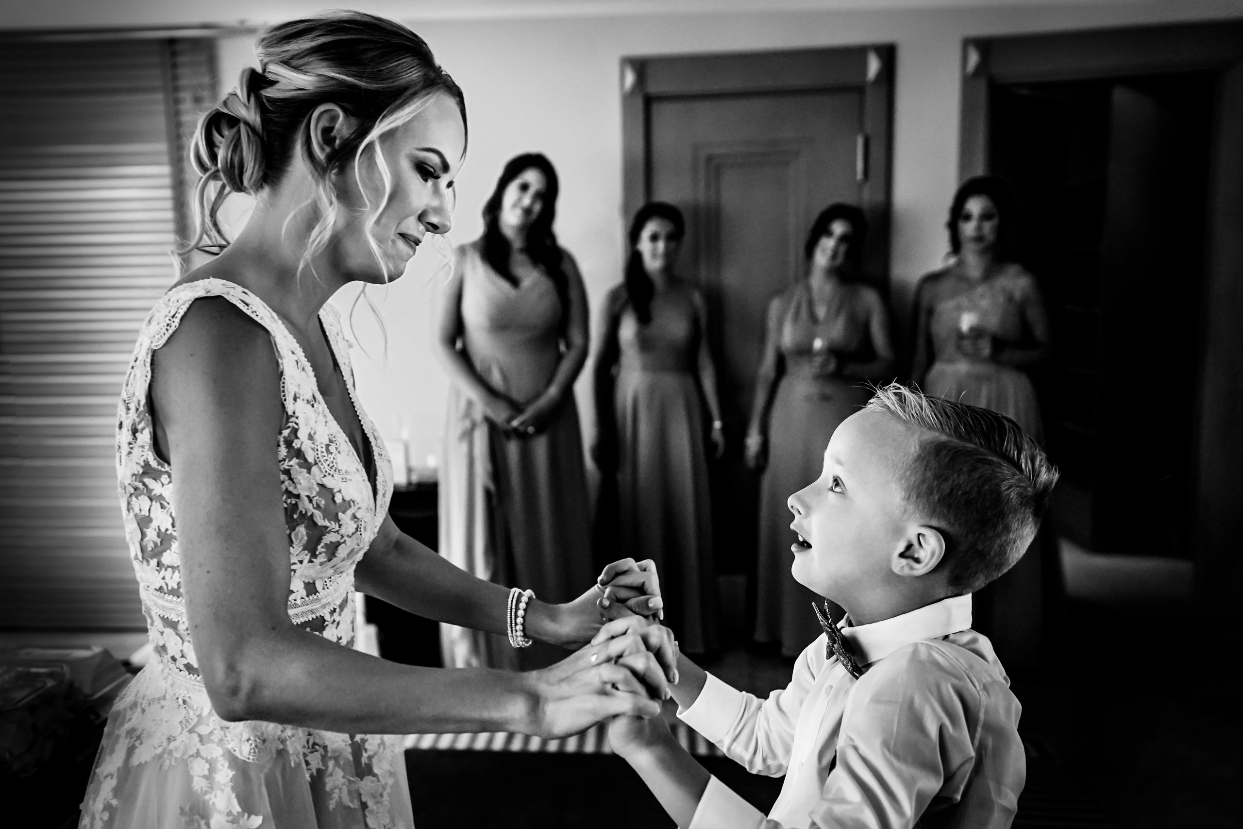 Boy holds his mother's hands as they share a moment before the wedding.