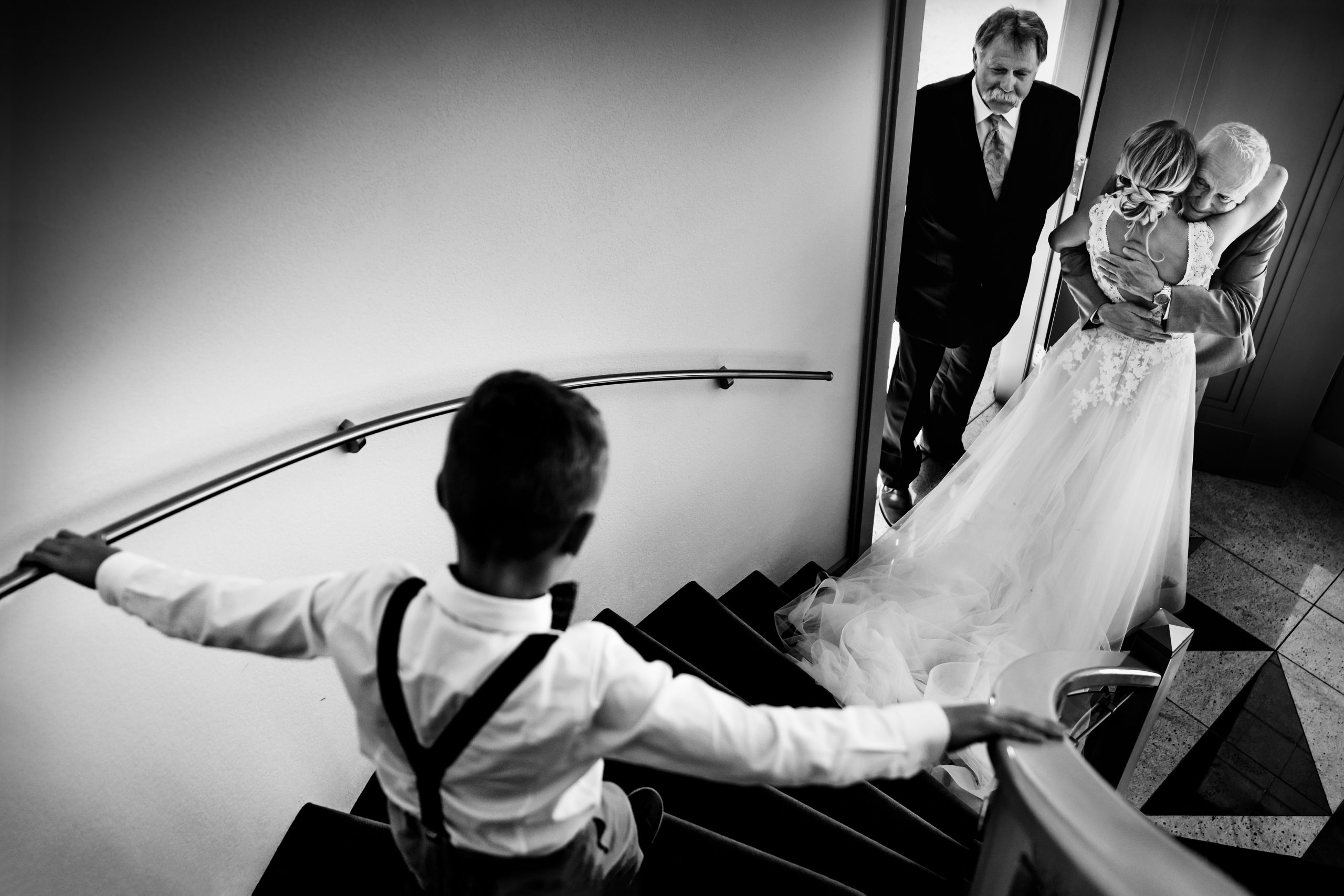 Boy follows bride down stairs.