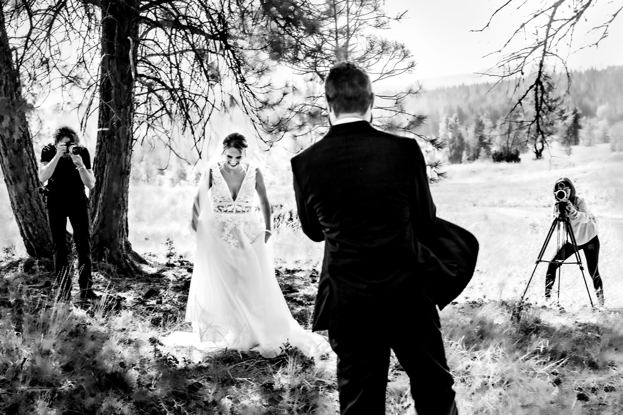 Photographers capture the moment the groom sees the bride for the first time.
