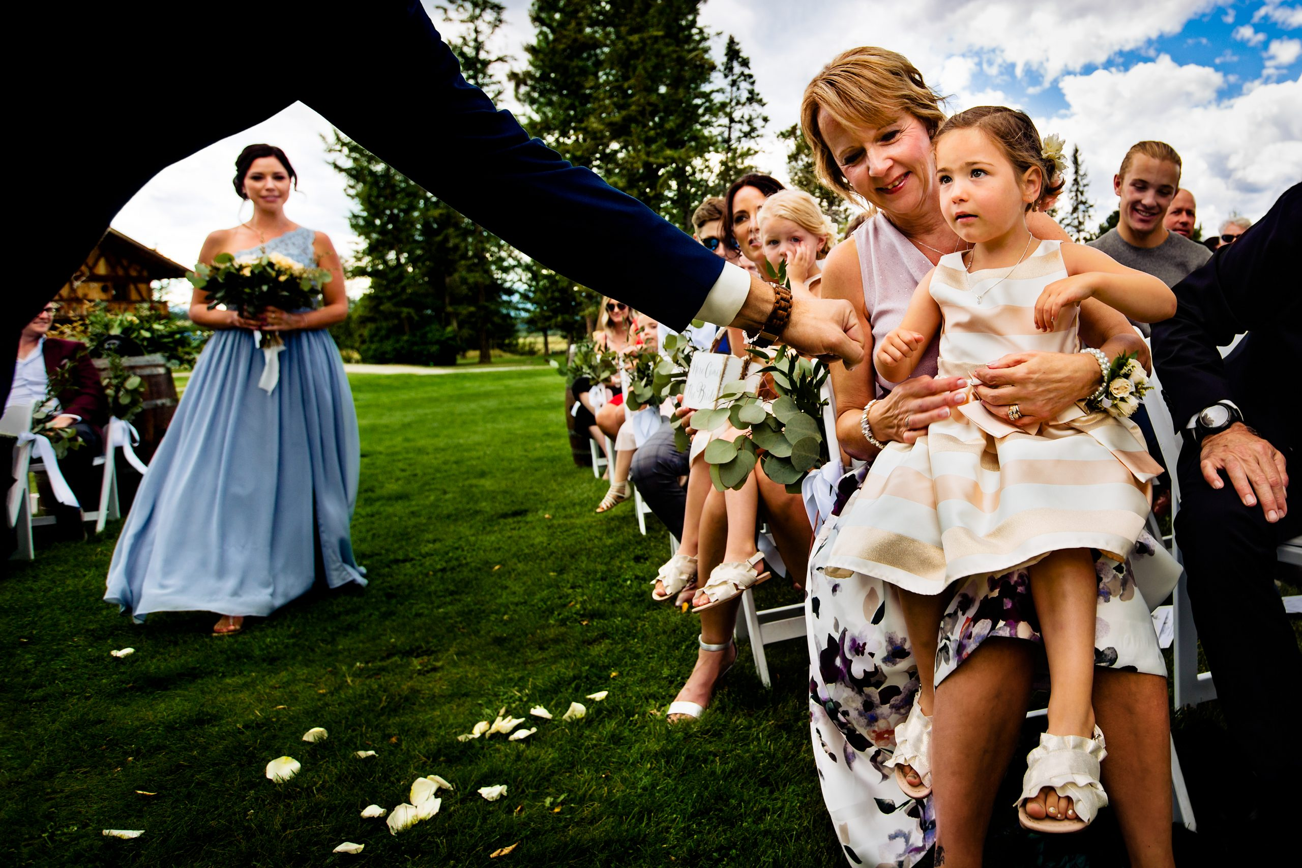 Groom offers a fist bump to flower girl in the front row.