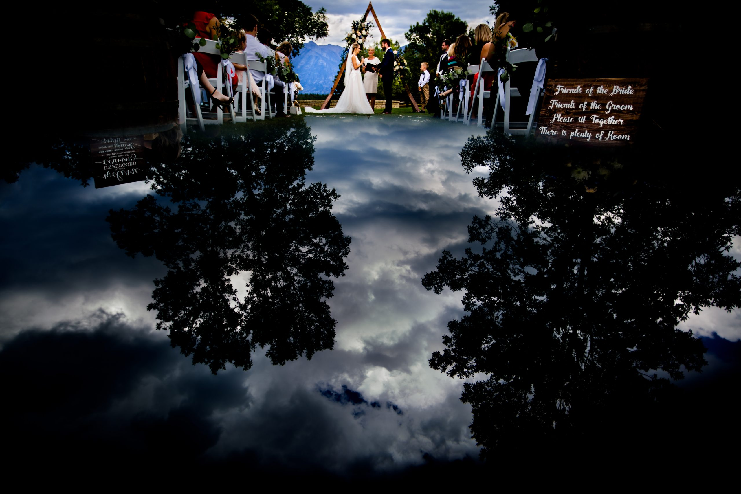 Sky and trees are reflected on a couple's wedding ceremony.