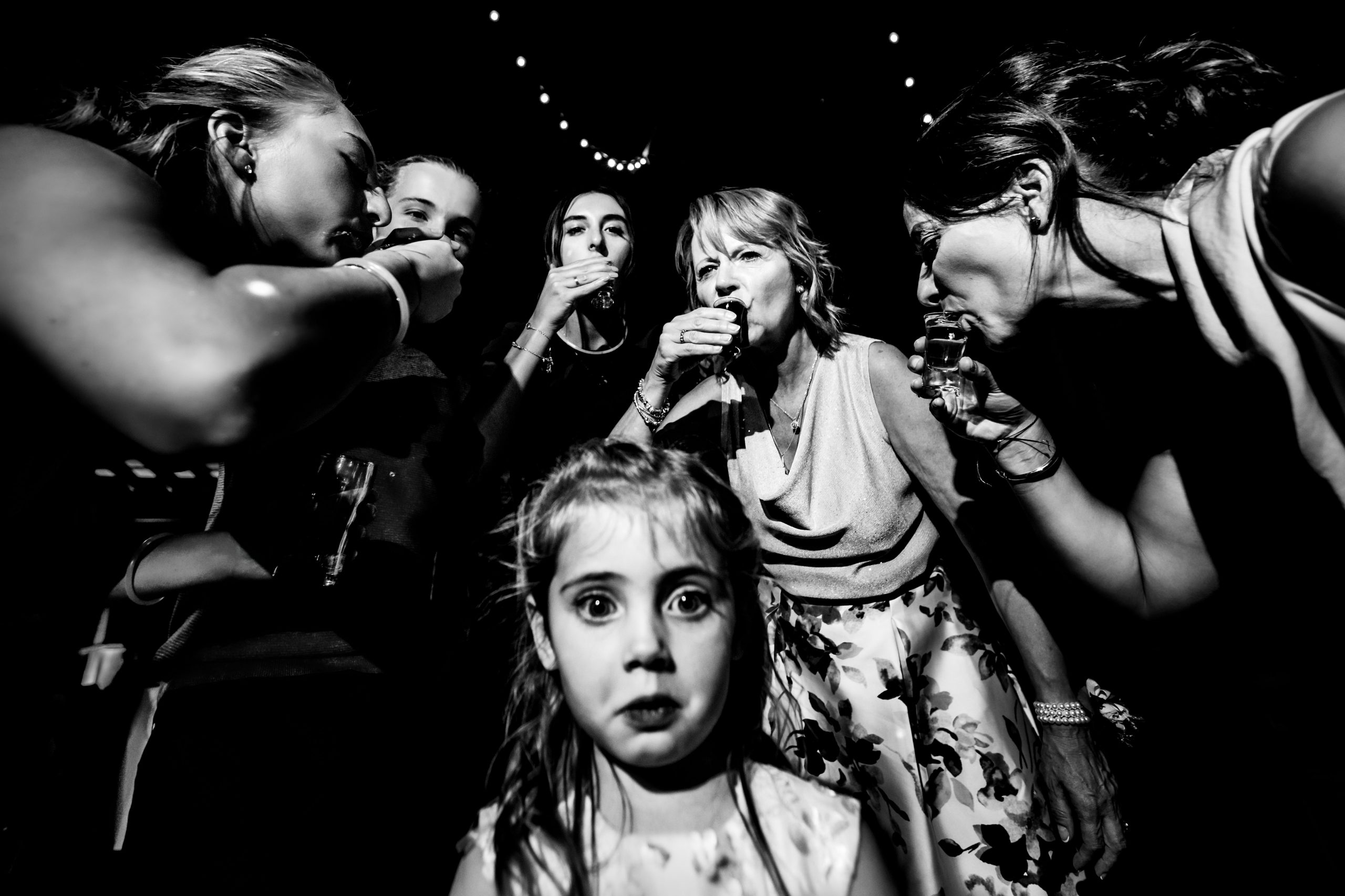 Young girl is surrounded by weddings guests having drinks.